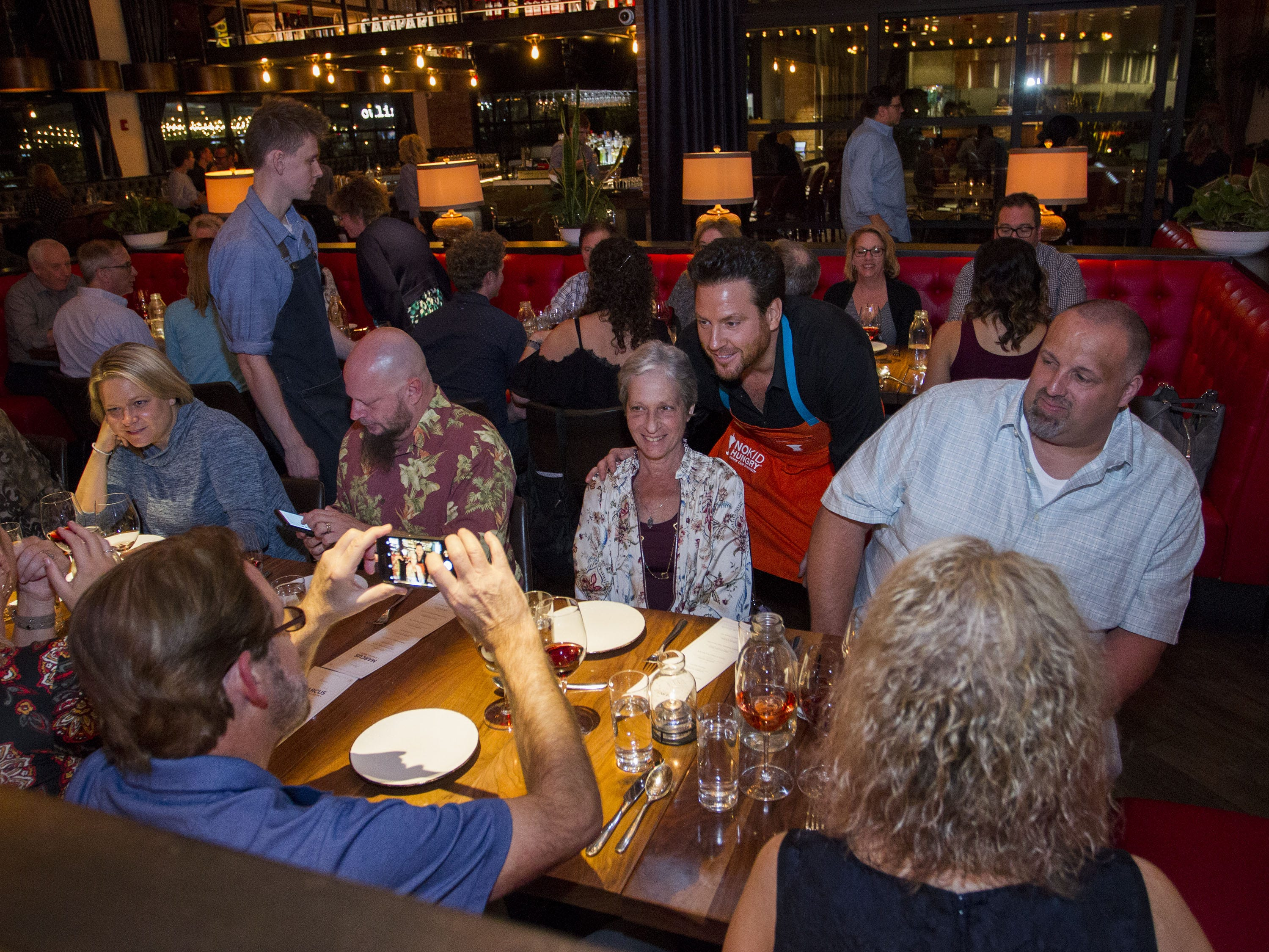 Chef Scott Conant poses with dinner guests during the exclusive kickoff dining event at Mora Italian for azcentral Wine & Food Experience.