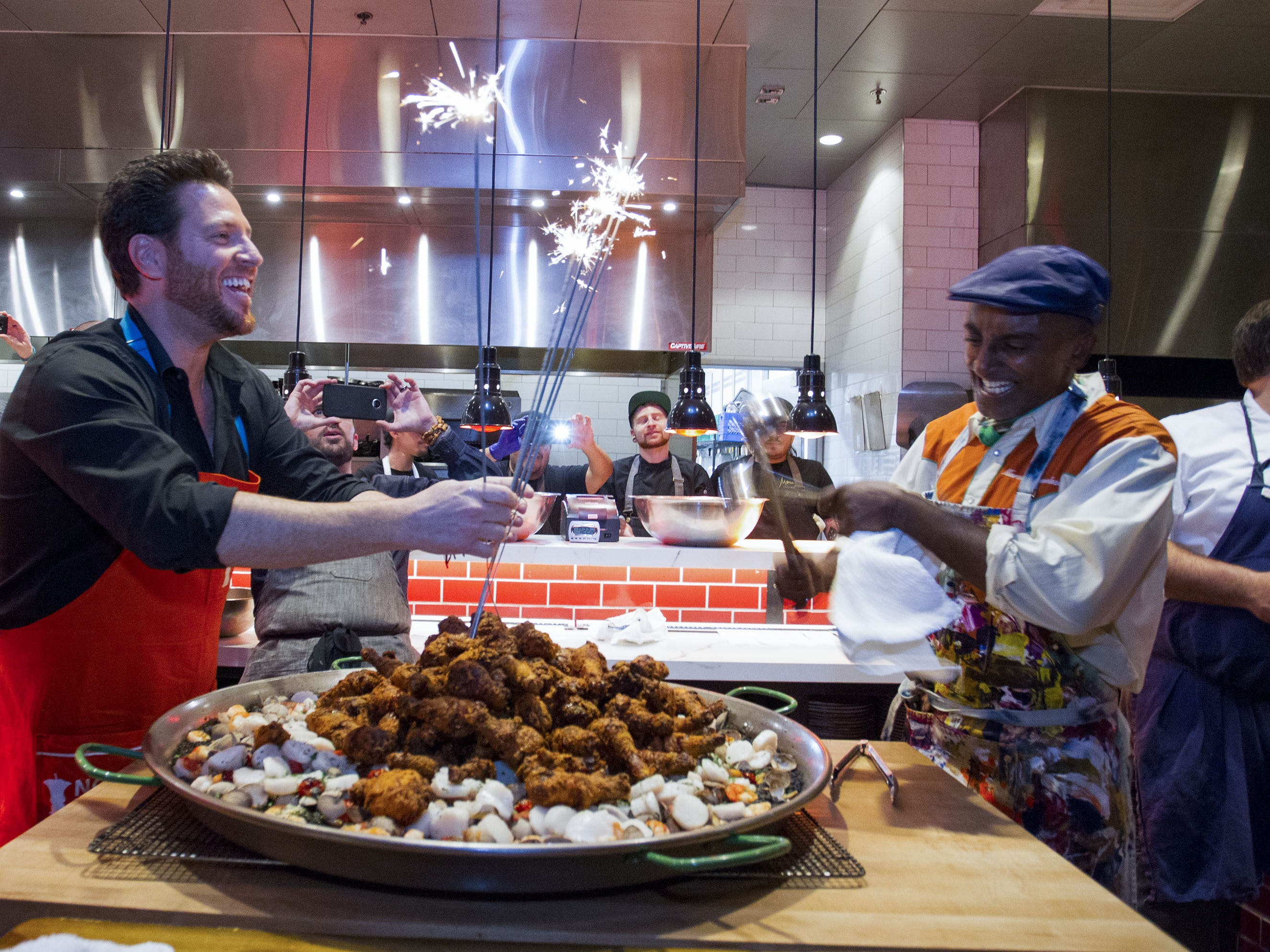 Chefs Scott Conant and Marcus Samuelsson light sparklers as they prepare to serve fried chicken paella to guests during the exclusive kickoff dinner event at Mora Italian for azcentral Wine & Food Experience.