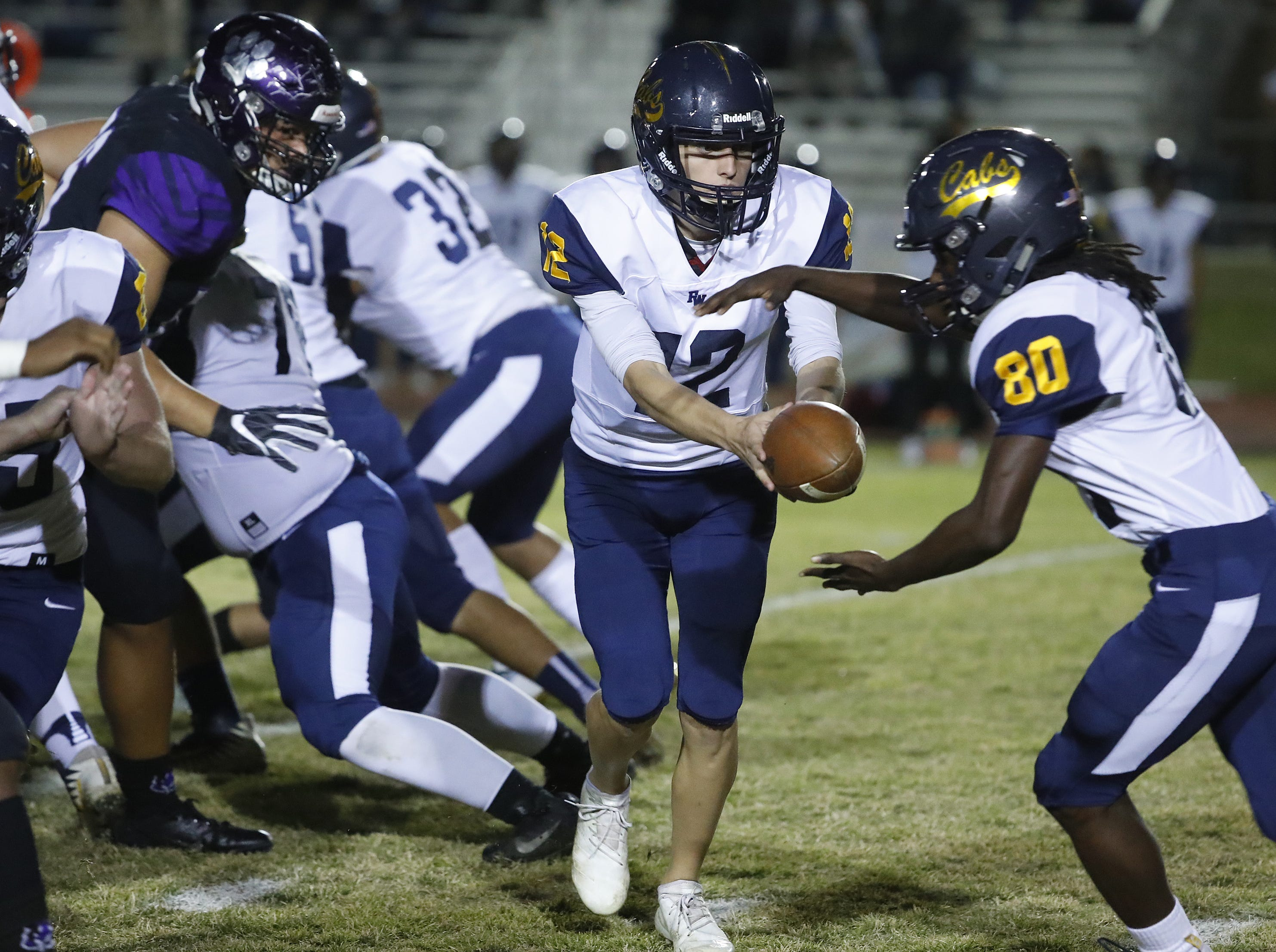 Flowing Wells' Zachary Jurado (12) hands the ball off to Estevan Aragon (20) during the first round of the AIA State Football Playoffs against Millennium at Millennium High School in Goodyear, Ariz. on Nov. 2, 2018.