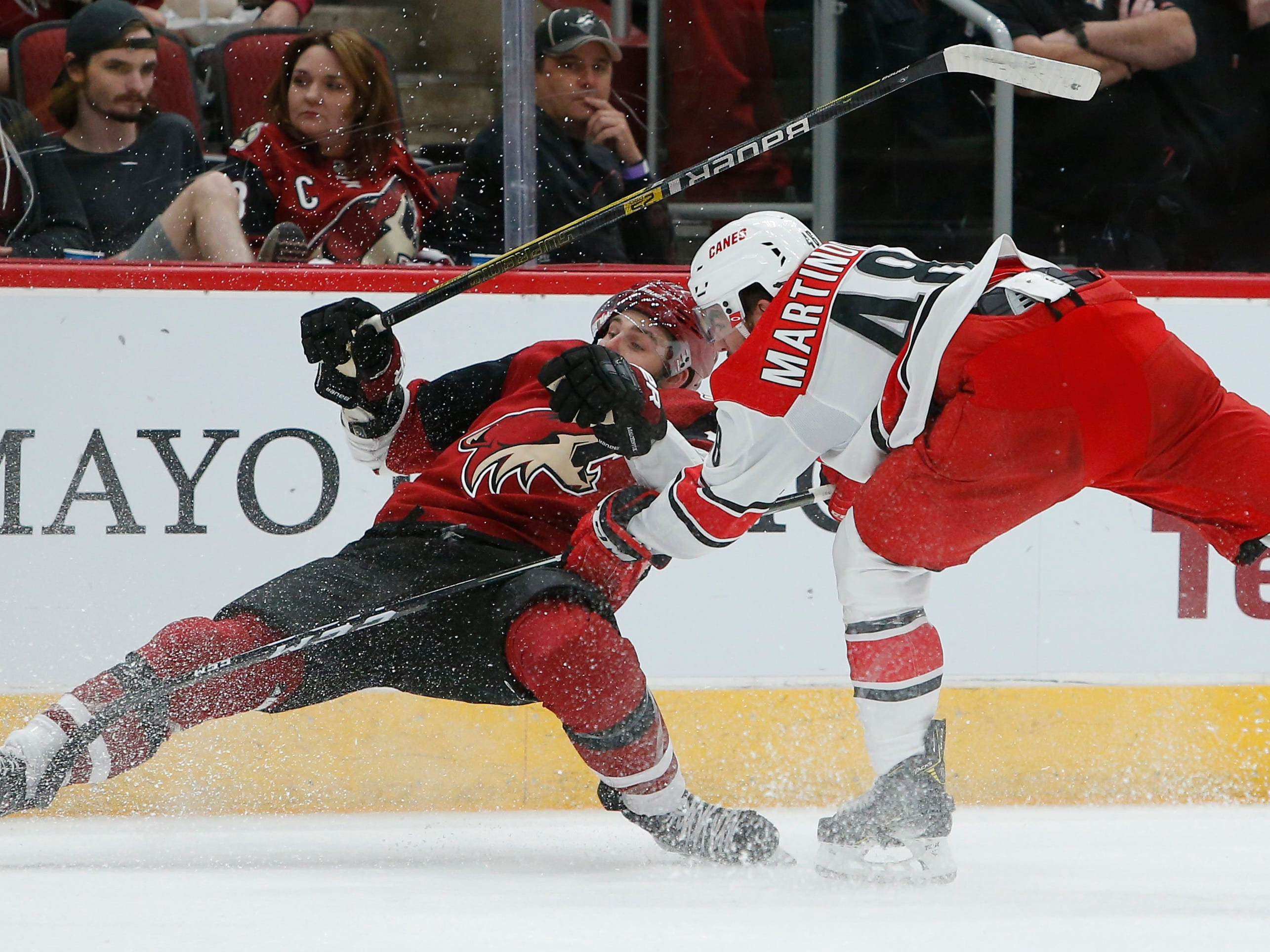 Carolina Hurricanes left wing Jordan Martinook (48) drags down Arizona Coyotes center Alex Galchenyuk for a tripping penalty during the first period of an NHL hockey game Friday, Nov. 2, 2018, in Glendale, Ariz. (AP Photo/Rick Scuteri)