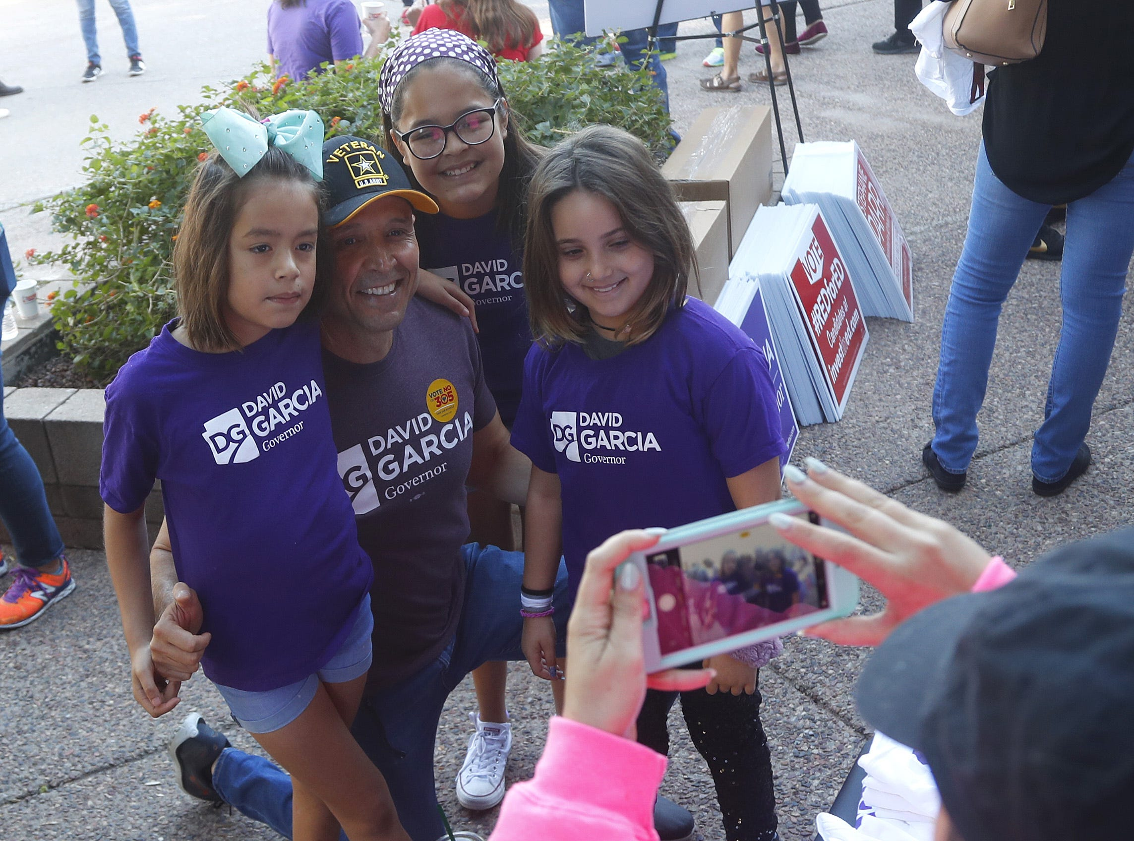 Ariel Rosen (in pink) takes a picture of her daughter Emunah, 9 (on right) with David Garcia and his two daughters Olivia (L) and Lola (center) outside the Arizona Education Association offices in Phoenix on November 3, 2018.