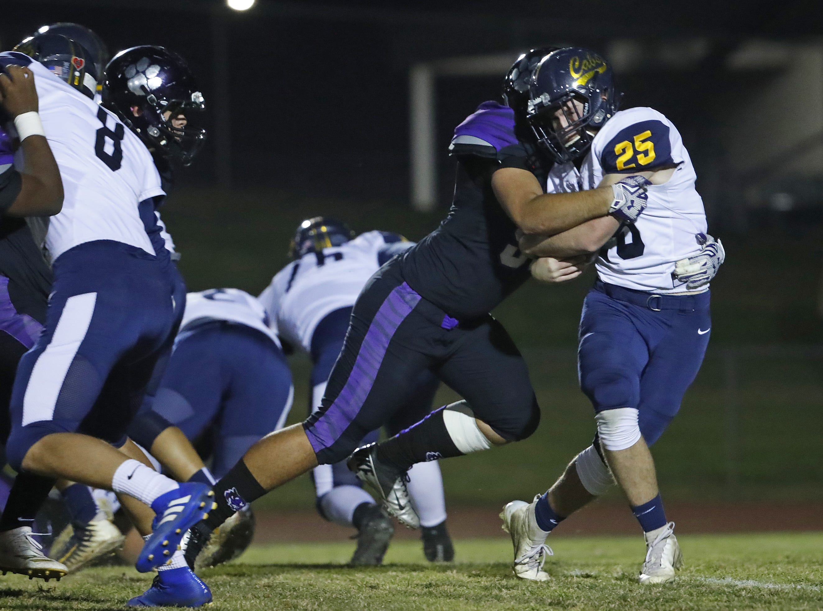 Millennium's Cristian Rodriguez (50) tackles Flowing Wells' Blake Bishop (25) during the first round of the AIA State Football Playoffs at Millennium High School in Goodyear, Ariz. on November 2, 2018.