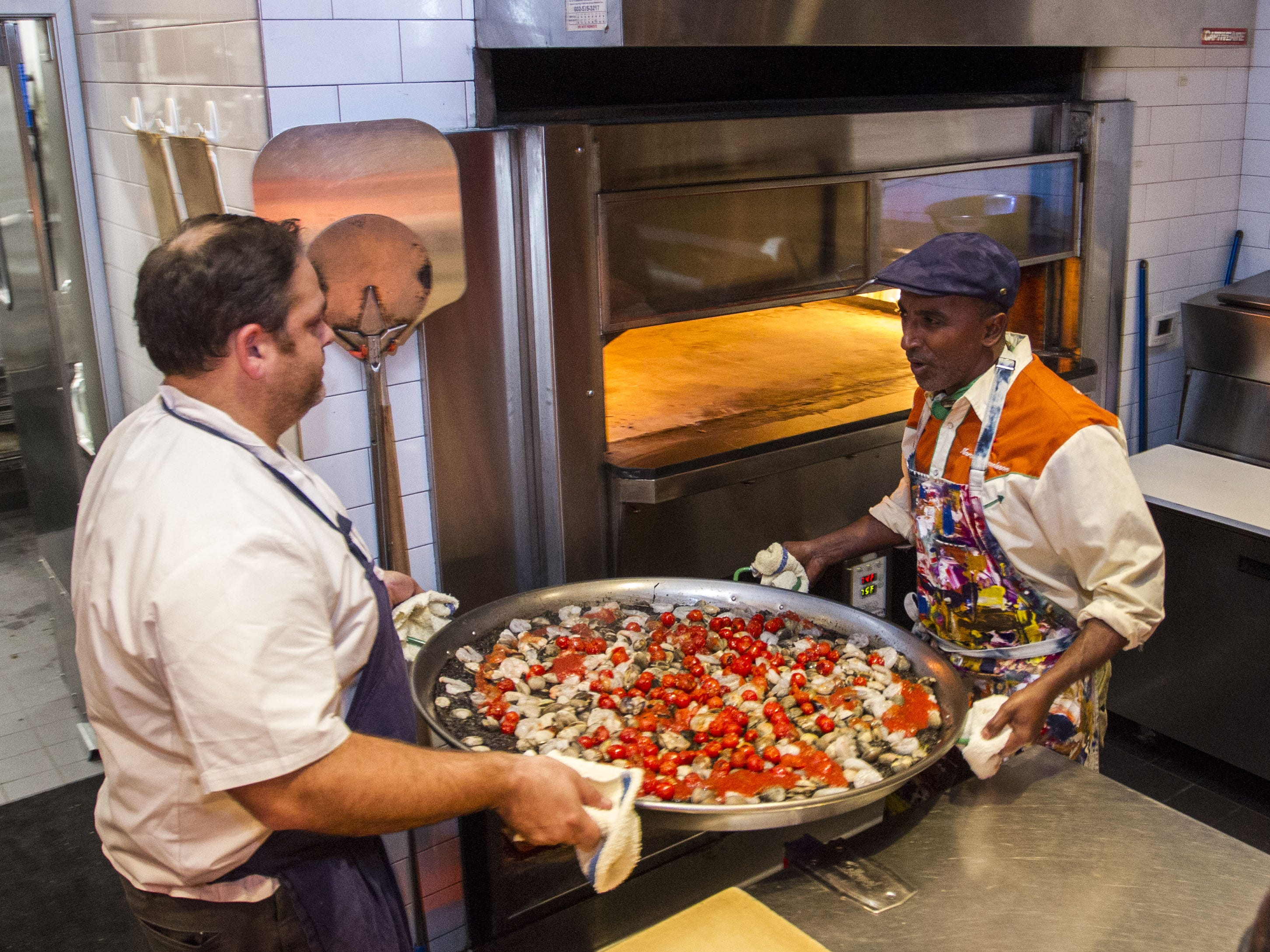 Chef Marcus Samuelsson gets some help placing the paella in the oven during the exclusive kickoff dining event at Mora Italian for azcentral Wine & Food Experience.