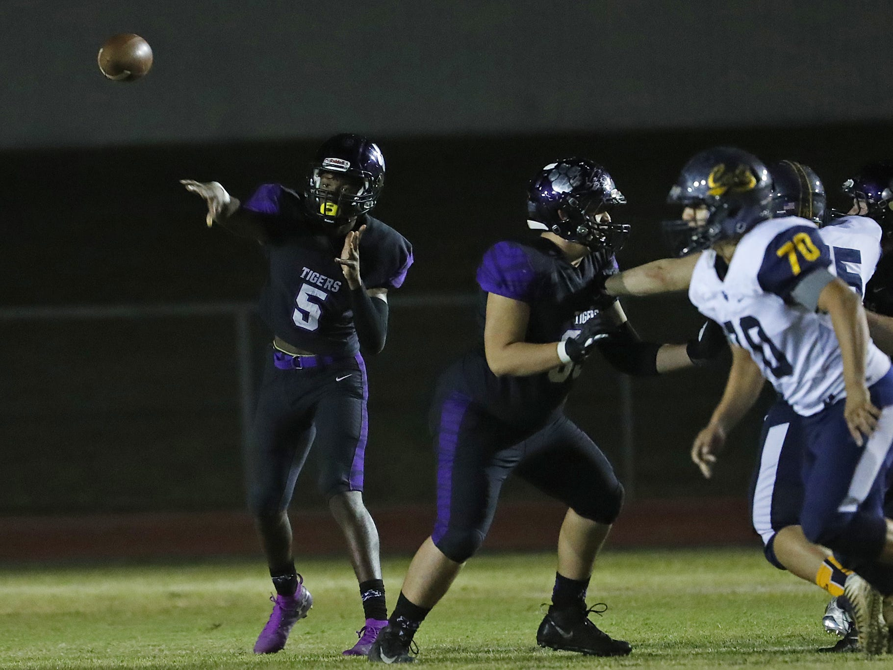 Millennium's Zareq Brown (5) throws a pass against Flowing Wells during the first round of the AIA State Football Playoffs at Millennium High School in Goodyear, Ariz. on Nov. 2, 2018.