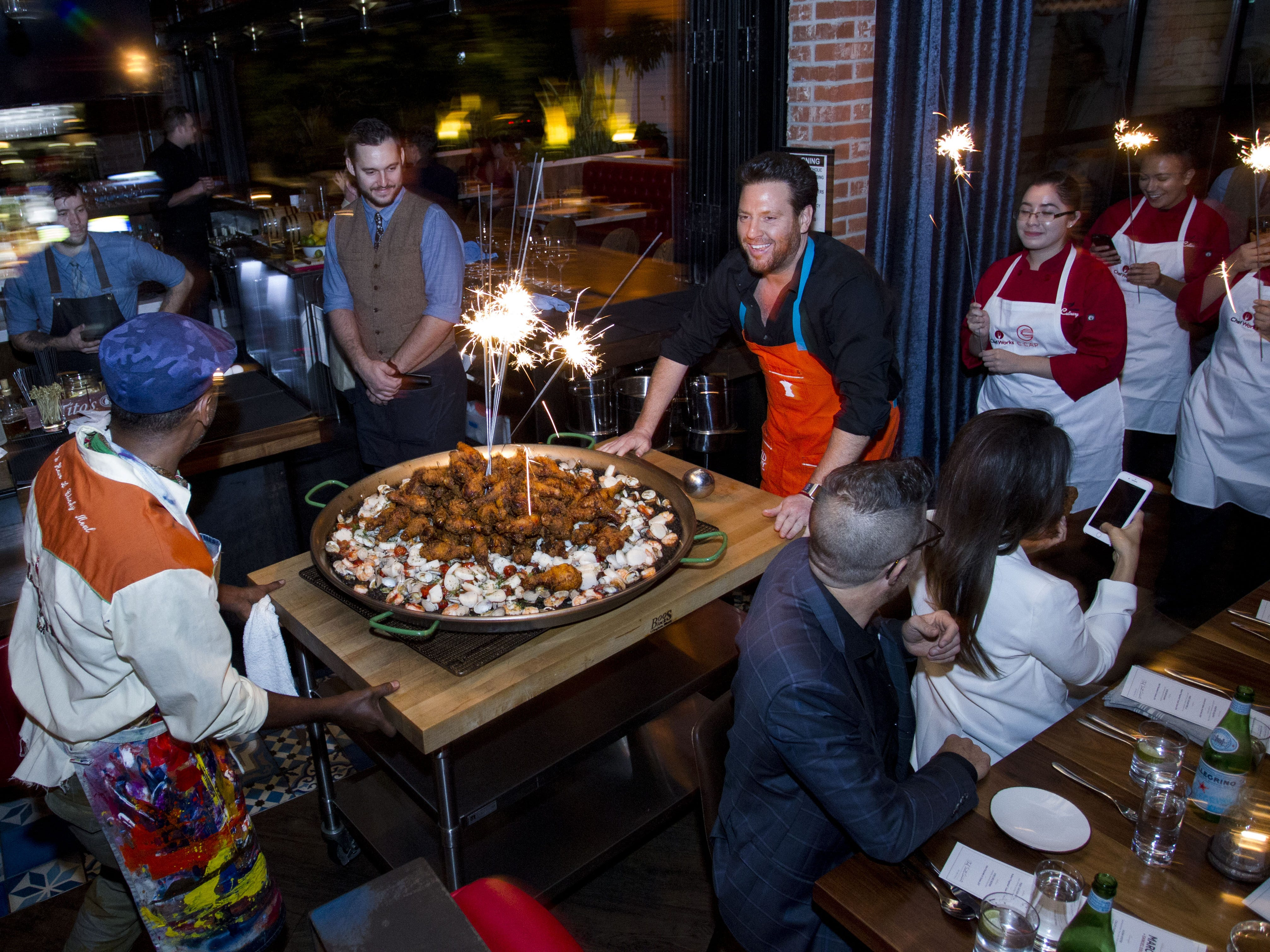 Chefs Scott Conant and Marcus Samuelsson show off their fried chicken paella, the main entree served to guests during the exclusive kickoff dinner event at Mora Italian for azcentral Wine & Food Experience.