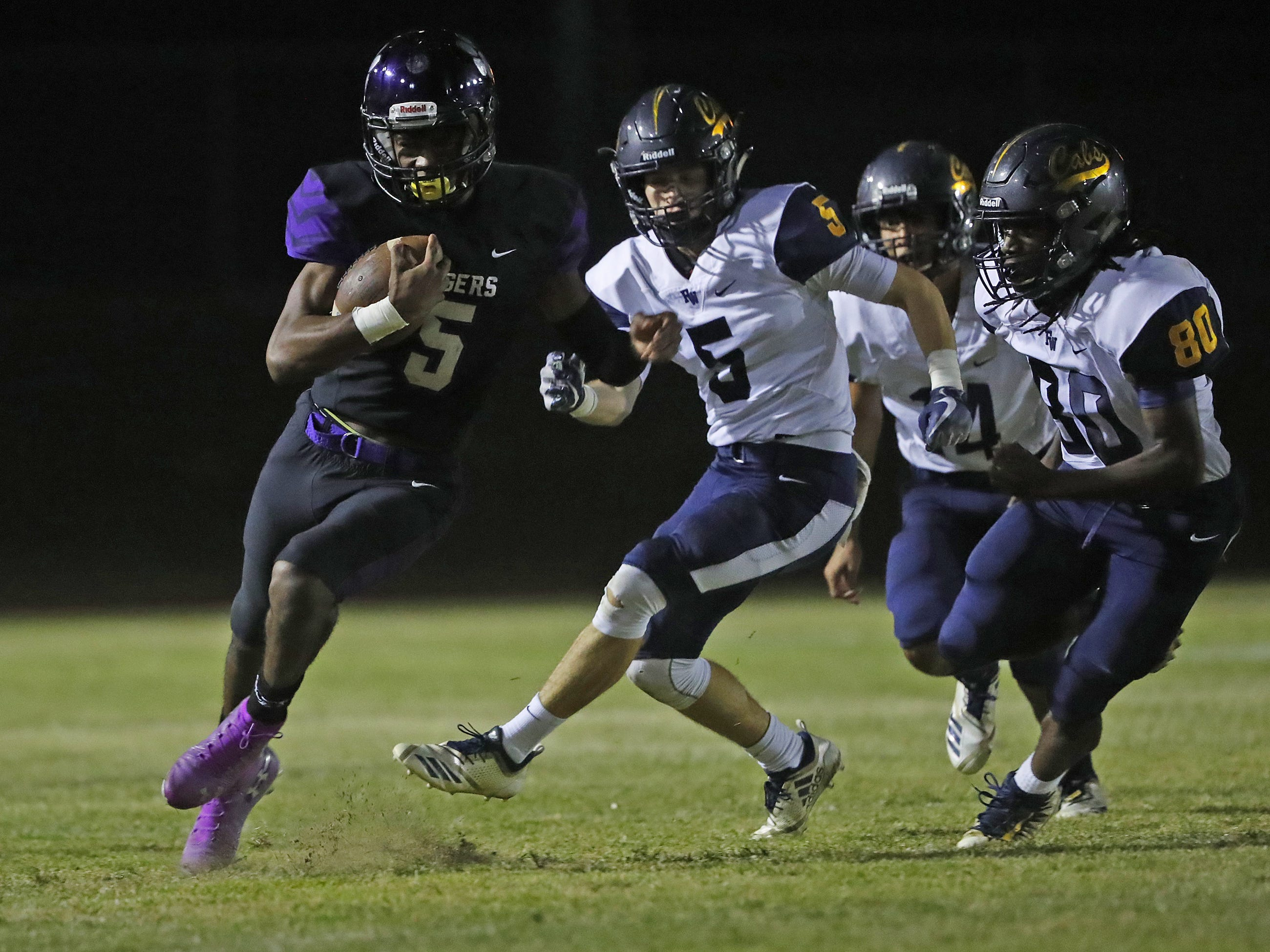 Millennium's Zareq Brown (5) runs for a first down past Flowing Wells' Isaiah Williams-Russell (80) during the first round of the AIA State Football Playoffs at Millennium High School in Goodyear, Ariz. on Nov. 2, 2018.