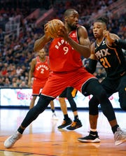 Raptors big man Serge Ibaka backs down Suns forward Richaun Holmes during the first half of a game Friday.