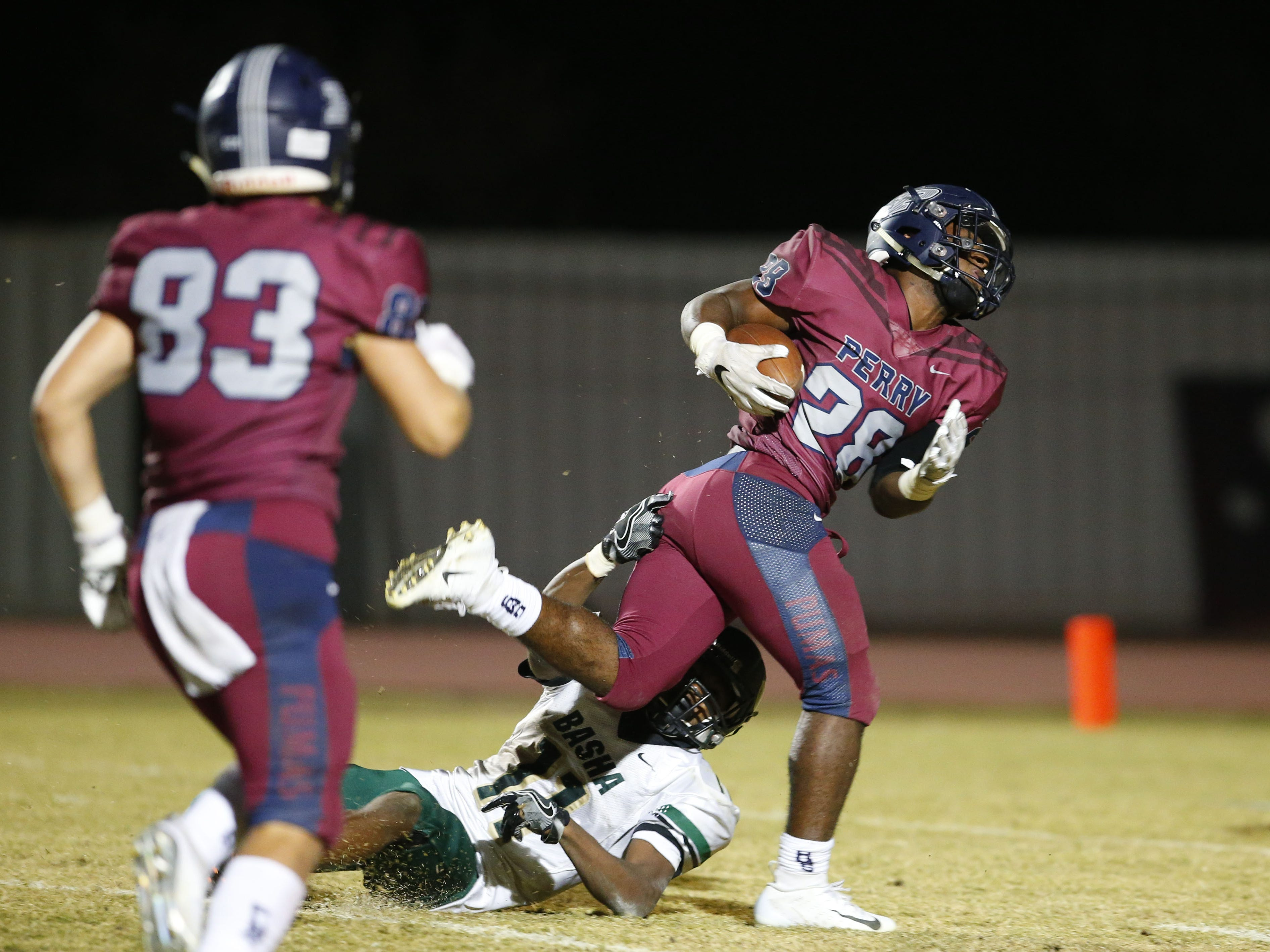 Perry running back Jalen Young (28) breaks an attempted  tackle by Bashas Andrell Barney (11) to score a touchdown during a football game at Perry High School on Nov. 2. #azhsfb