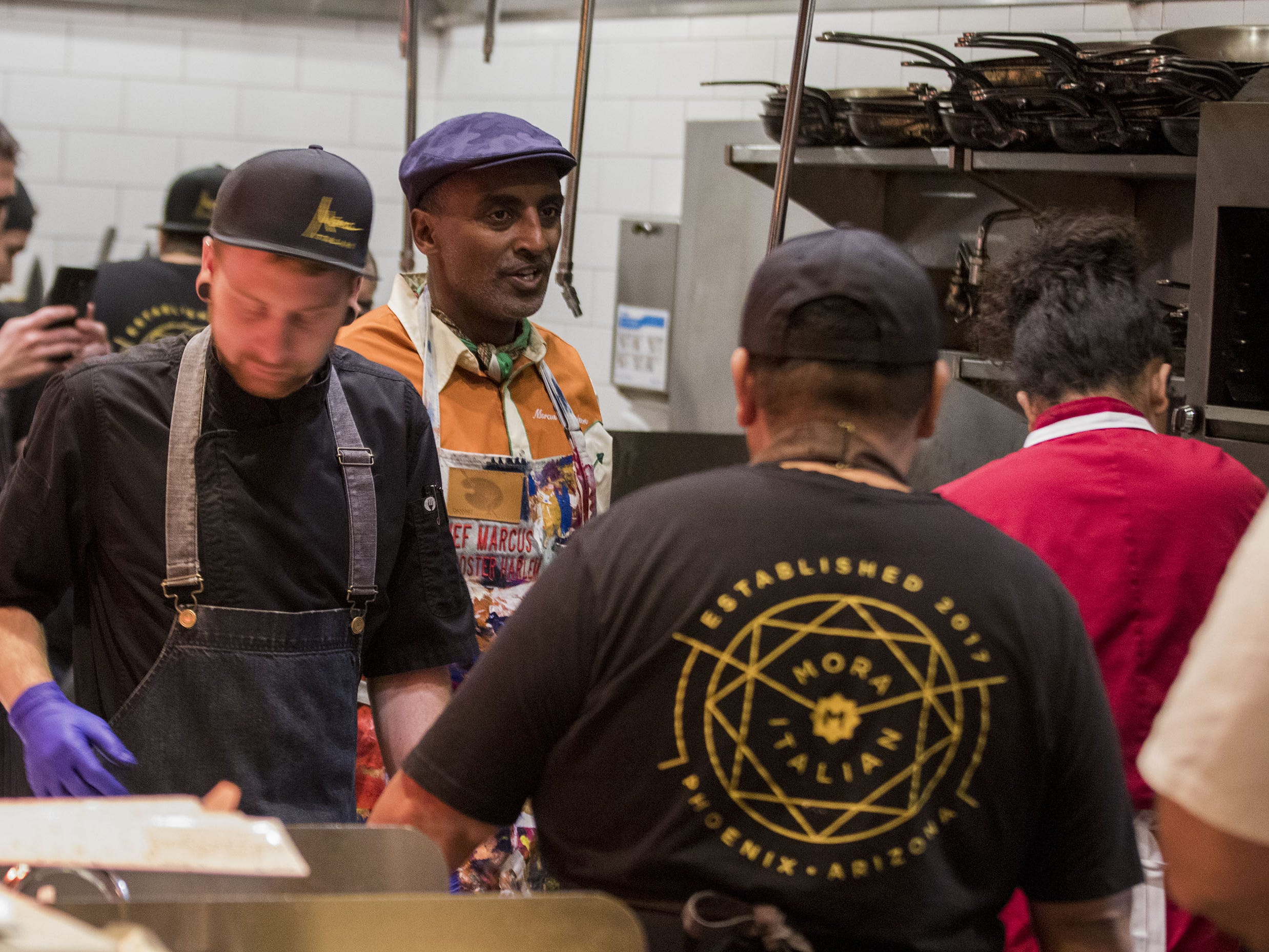 Chef Marcus Samuelsson keeps an eye on things in the kitchen during the exclusive kickoff dining event at Mora Italian for azcentral Wine & Food Experience.