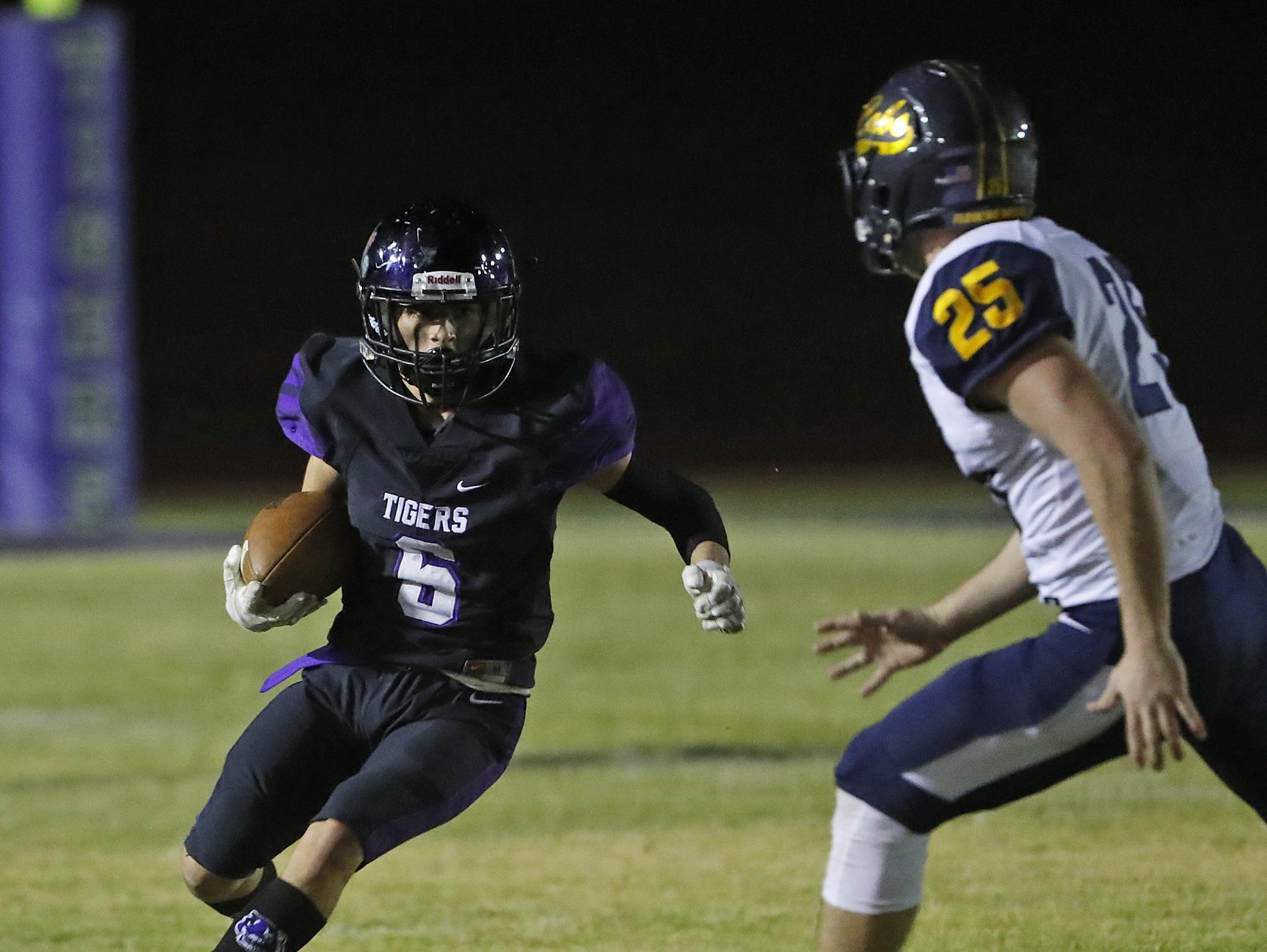 Millennium's Joseph Rosales (6) heads downfield against Flowing Wells' Blake Bishop (25) during the first round of the AIA State Football Playoffs at Millennium High School in Goodyear, Ariz. on Nov. 2, 2018.