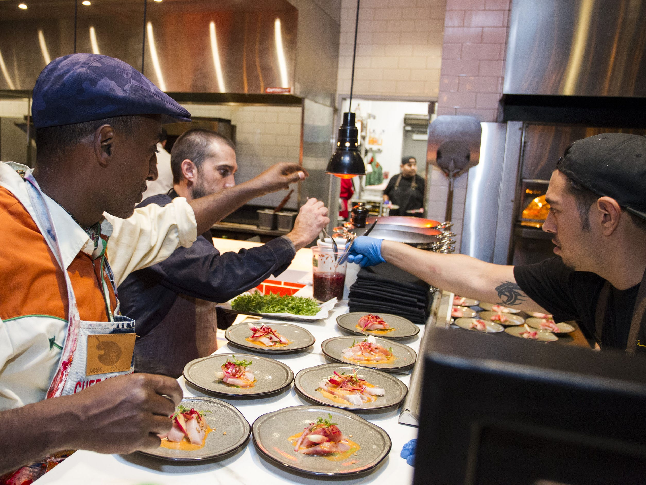 Chef Marcus Samuelsson gives advice to chefs as they prep kampachi aguachile during the exclusive kickoff dining event at Mora Italian for azcentral Wine & Food Experience.