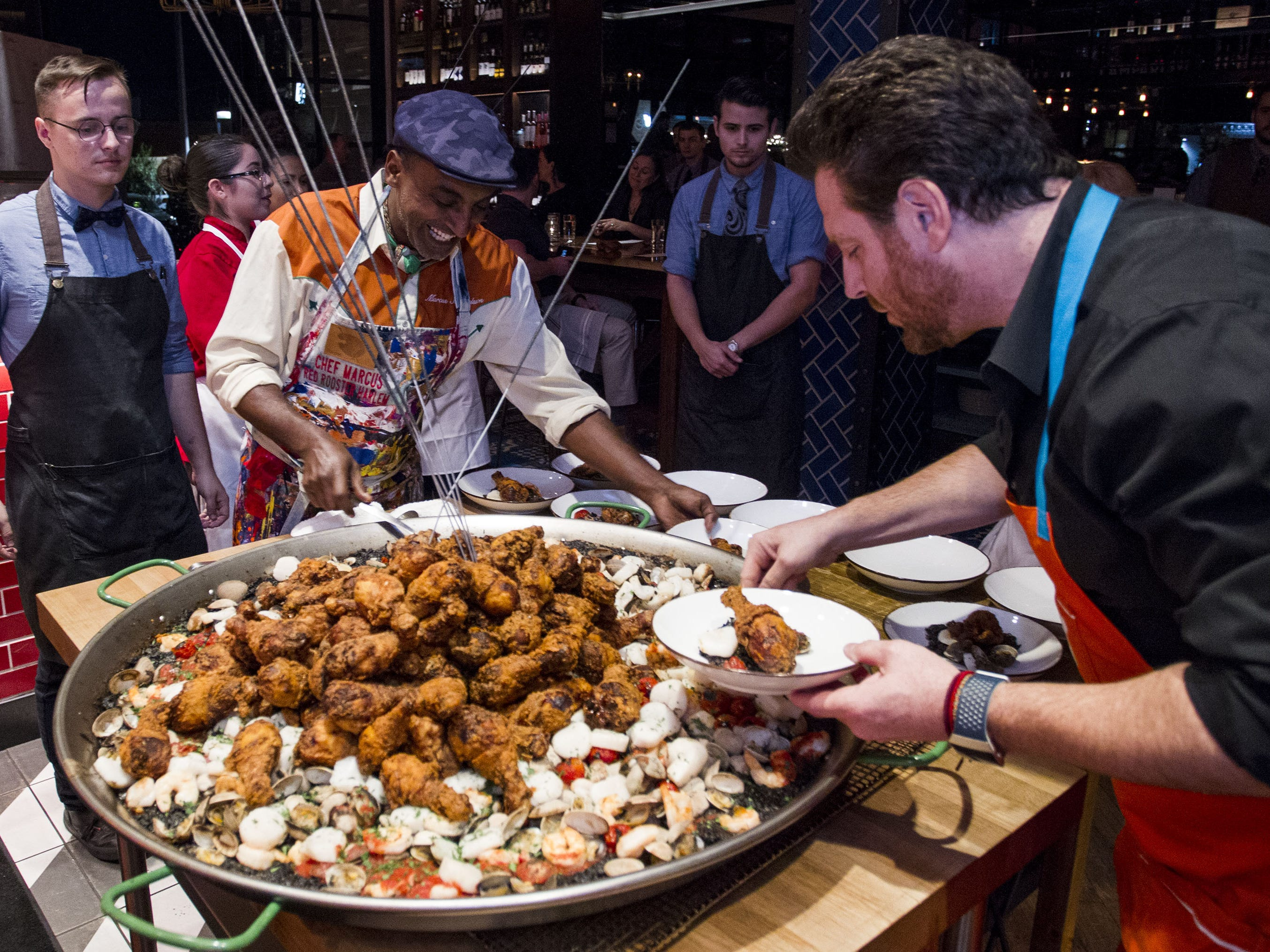 Chefs Marcus Samuelsson and Scott Conant serve their fried chicken paella to dinner guests during the exclusive kickoff dining event at Mora Italian for azcentral Wine & Food Experience.