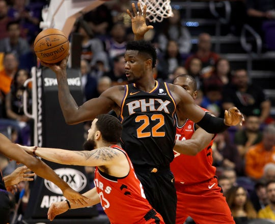Phoenix Suns center Deandre Ayton (22) looks to pass as Toronto Raptors forward Serge Ibaka, right, and guard Fred VanVleet (23) defend during the first half of an NBA basketball game, Friday, Nov. 2, 2018, in Phoenix.