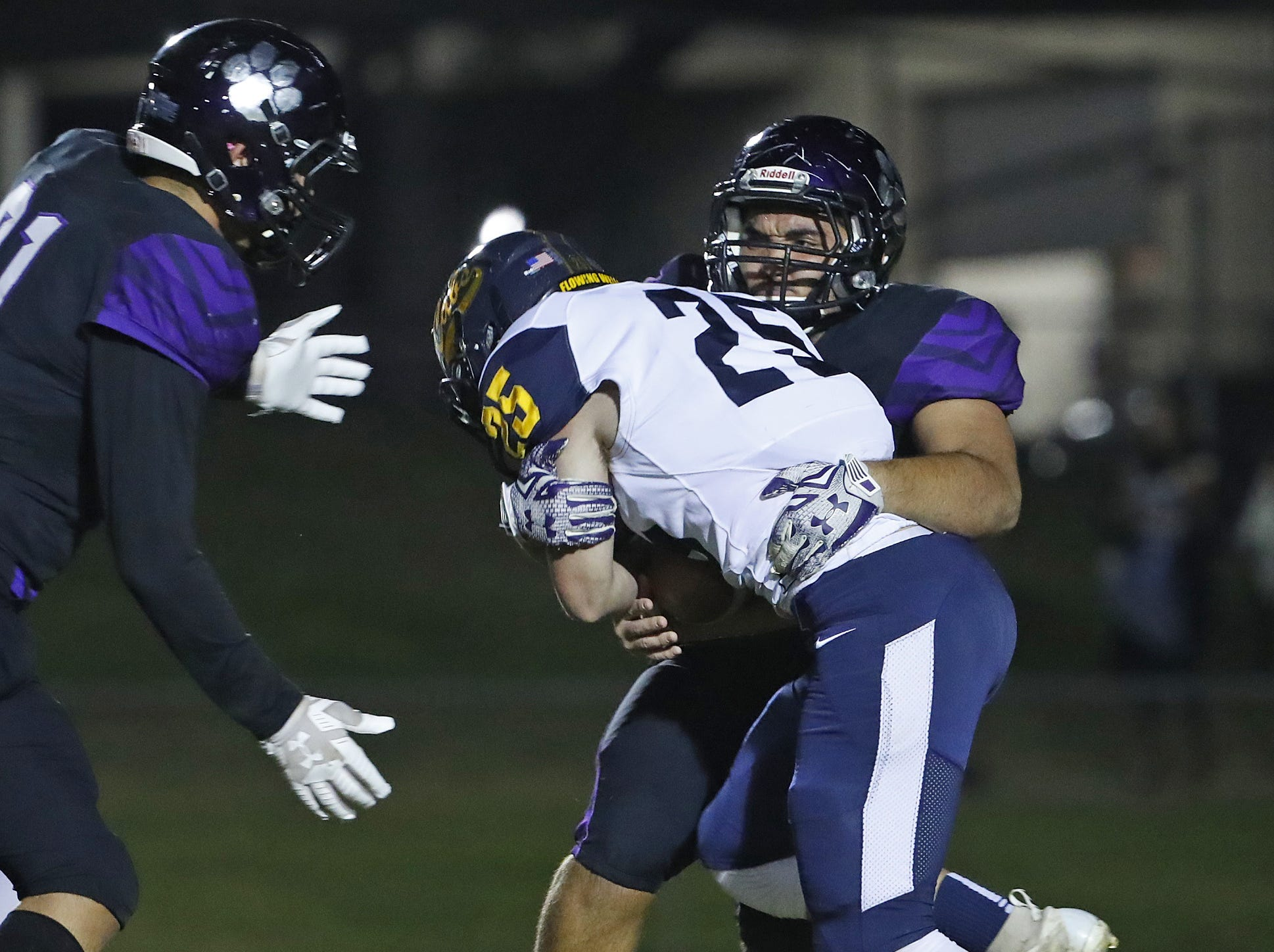 Millennium's Cristian Rodriguez (50) tackles Flowing Wells' Blake Bishop (25) during the first round of the AIA State Football Playoffs at Millennium High School in Goodyear, Ariz. on Nov. 2, 2018.