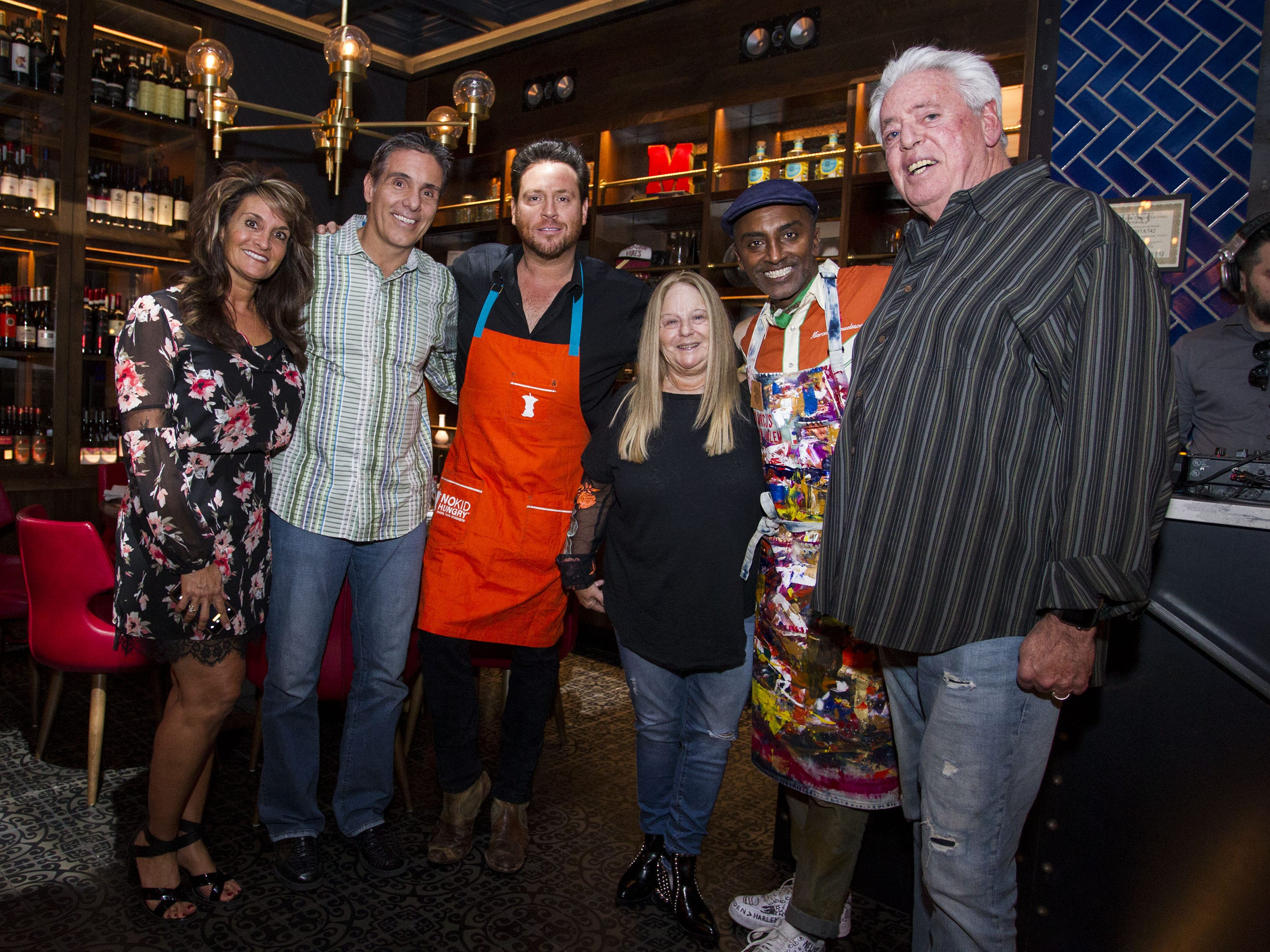 Chefs Scott Conant and Marcus Samuelsson pose for a photo with Kerri and John Lombardi (left) and Judy and Rob Miller (right) during the exclusive kickoff dining event at Mora Italian for azcentral Wine & Food Experience.