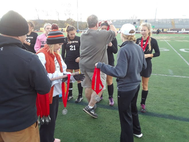 Palmyra coach Kent Harshman hands out runner-up medals to his team following its 3-0 loss to Donegal in the 2A district title game at Milton Hershey on Saturday.