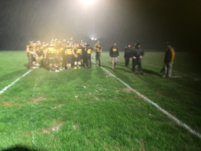 The Elco football team holds its final postgame huddle in a driving rainstorm after Friday night's 37-0 loss to Lampeter-Strasburg in the opening round of the district playoffs.