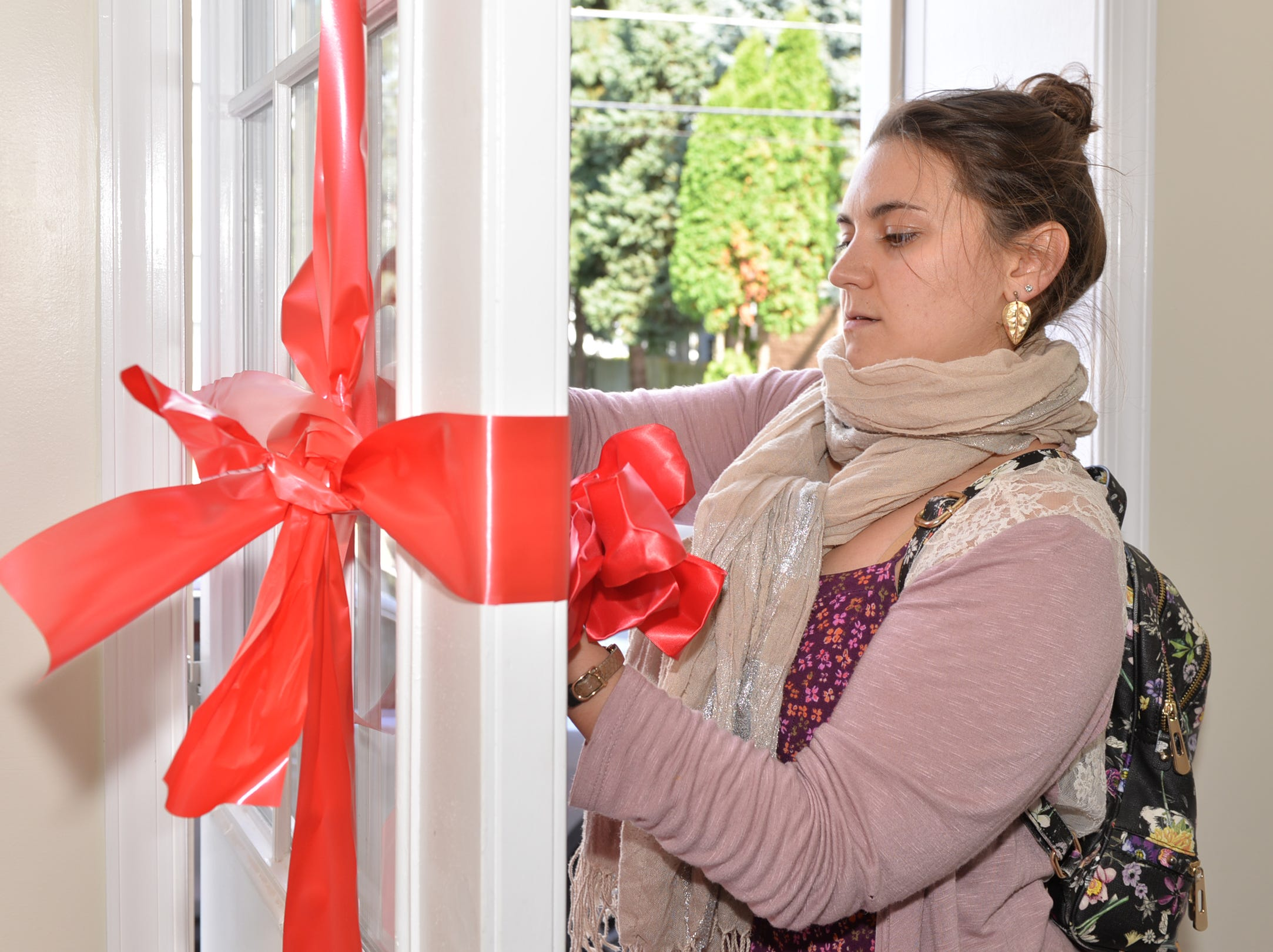 Allyson Wells, community outreach manager for Lancaster Lebanon Habitat for Humanity, ties a red bow on the front door of 1042 Lehman Street, Lebanon. The recently completed habitat home was presented to Enid Medero and her family on Saturday, November 3, 2018.