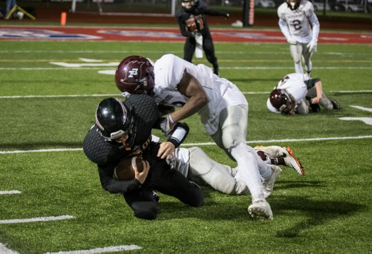 Marine City High School running back Charles Tigert (left) is tackled by Harper Woods running back Keambiroiroi Perdue during their division 5 finals match Friday, Nov. 2, 2018 at Memorial Stadium in Port Huron.