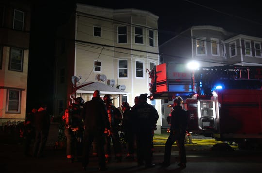 Firefighters stand outside a structure fire in a home on Mansion Street in the City of Poughkeepsie on Saturday evening. A fire was reported at around 5:53 p.m., according to Fire Chief Mark Johnson.