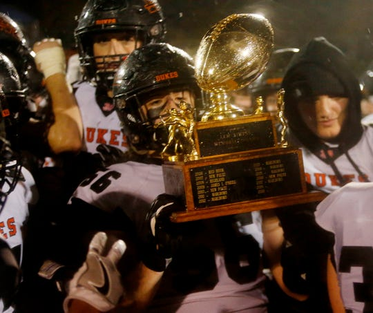 Marlboro senior Nick Esposito hoists the Section 9 Class B championship trophy after his teams win over O'Neill in the final on Nov. 2.