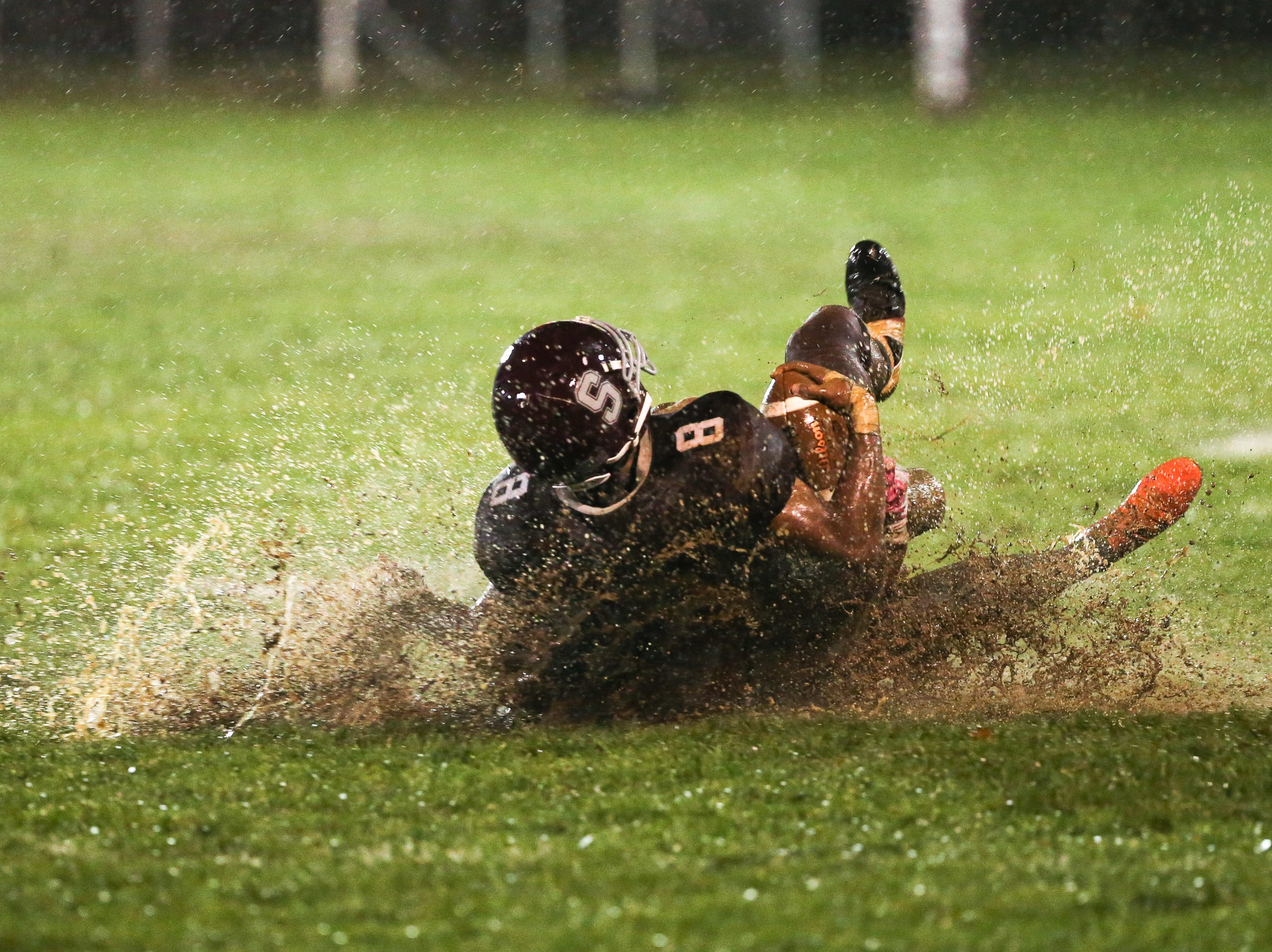 Senior Adam Houser slides through muddy grass while holding the ball. The Shippensburg Greyhounds defeated Northeastern, 6-0, in a playoff game in Shippensburg on Friday, Nov. 2, 2018.
