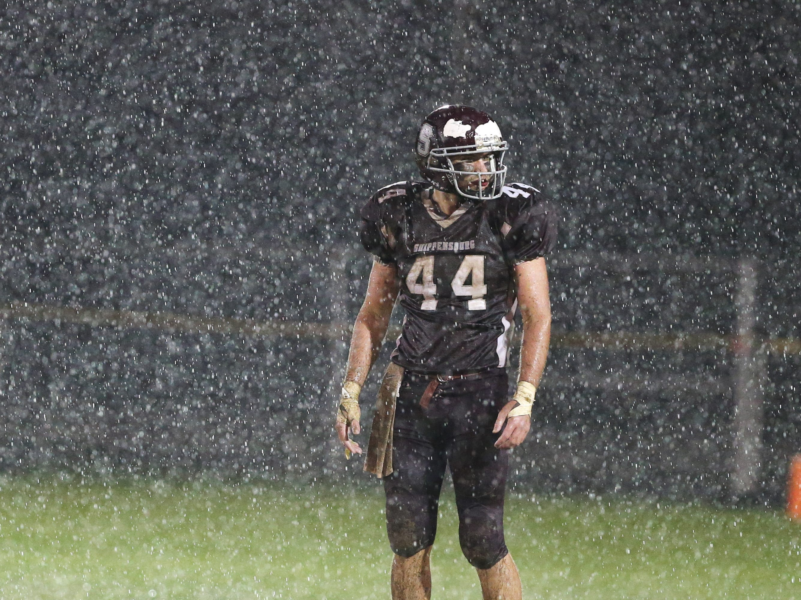 A player stands in the pouring rain. The Shippensburg Greyhounds defeated Northeastern, 6-0, in a playoff game in Shippensburg on Friday, Nov. 2, 2018.