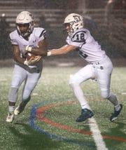 Chambersburg's Keyshawn Jones takes a handoff from QB Brady Stumbugh. Chambersburg Trojans dropped a close game 20-17 to Manheim Township Blue Streaks in the rain during PIAA District 3 playoff football on Friday, Nov. 2, 2018.