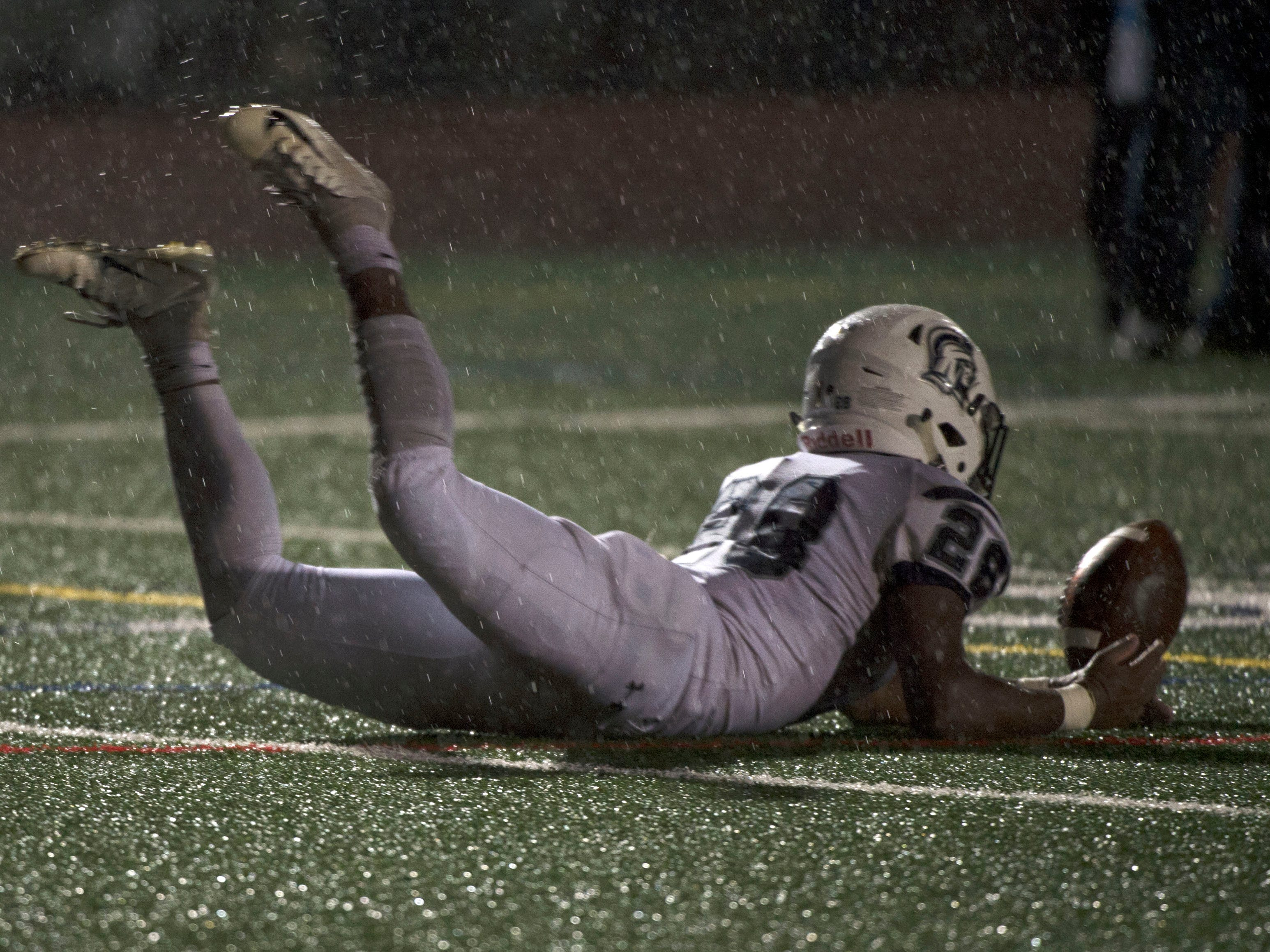 Chambersburg's Keyshawn Jones (28) slides in after the ball. Chambersburg Trojans dropped a close game 20-17 to Manheim Township Blue Streaks in the rain during PIAA District 3 playoff football on Friday, Nov. 2, 2018.