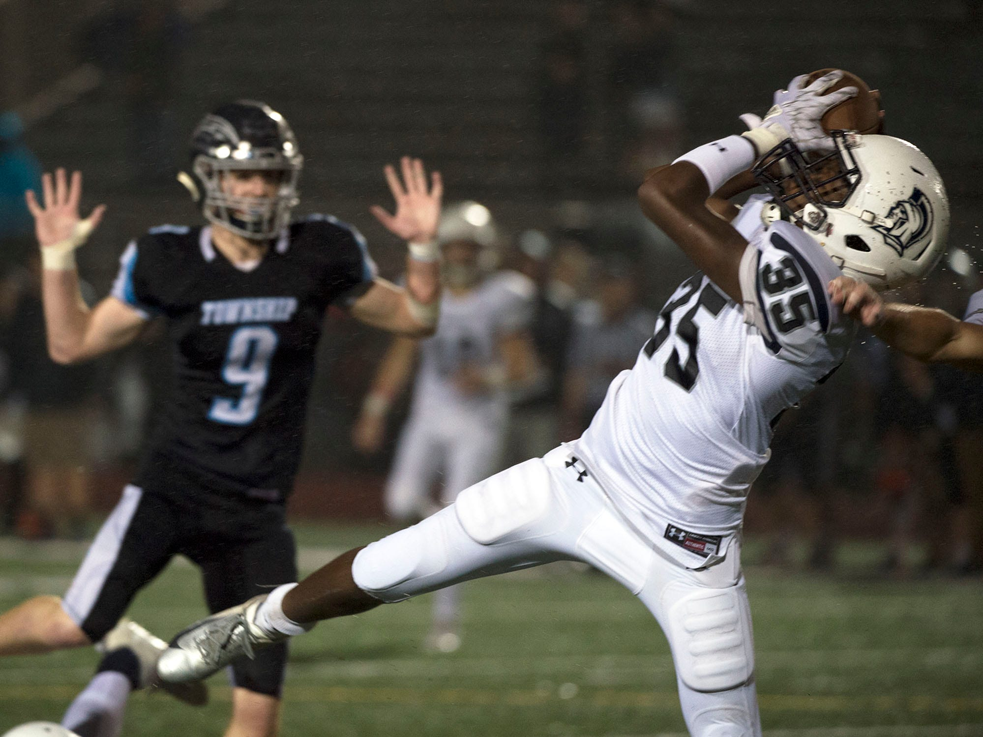 Chambersburg's DaQuan Rogers (35) catches a pass in front of Manheim Central's Jon Engel. Chambersburg Trojans dropped a close game 20-17 to Manheim Township Blue Streaks in the rain during PIAA District 3 playoff football on Friday, Nov. 2, 2018.