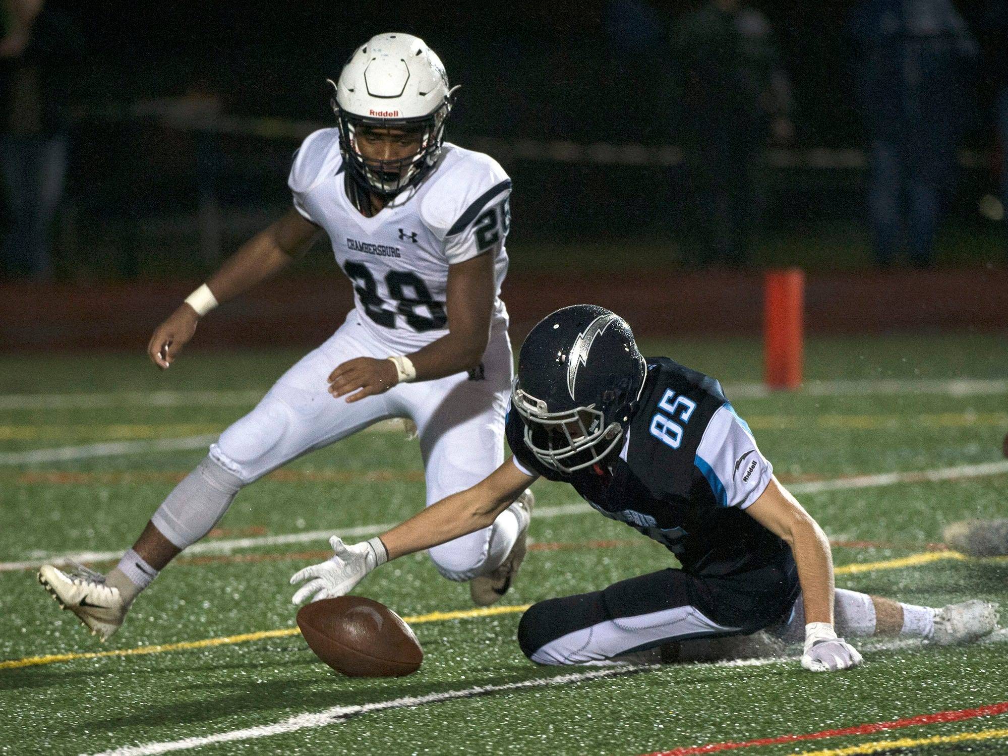 Chambersburg's Keyshawn Jones chases the ball with Adam Schlemmer (85) of Manheim Central. Chambersburg Trojans dropped a close game 20-17 to Manheim Township Blue Streaks in the rain during PIAA District 3 playoff football on Friday, Nov. 2, 2018.