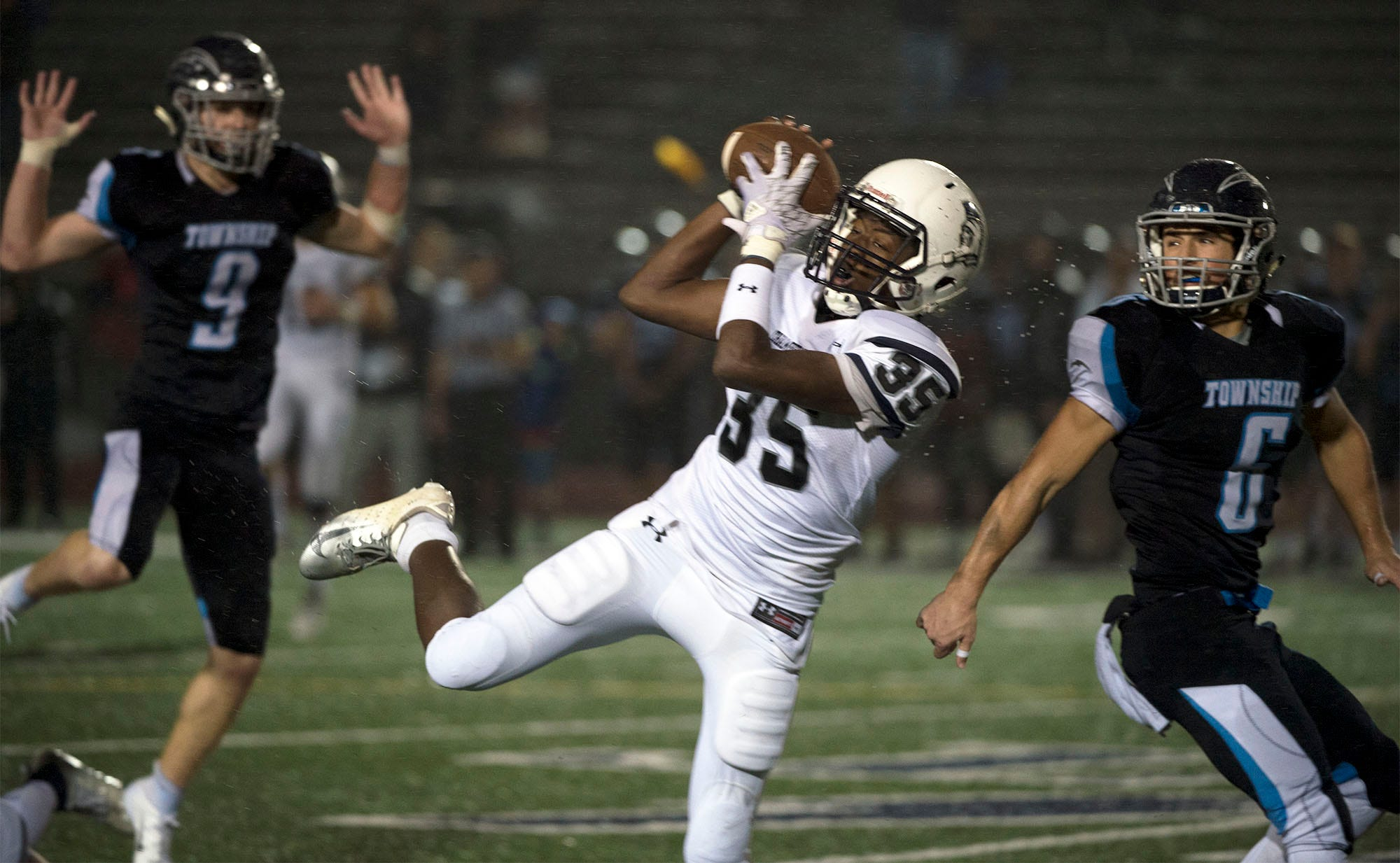 Chambersburg's DaQuan Rogers (35) catches a pass in front of Manheim Central's Brett Benjamin (6) and Jon Engel. Chambersburg Trojans dropped a close game 20-17 to Manheim Township Blue Streaks in the rain during PIAA District 3 playoff football on Friday, Nov. 2, 2018.