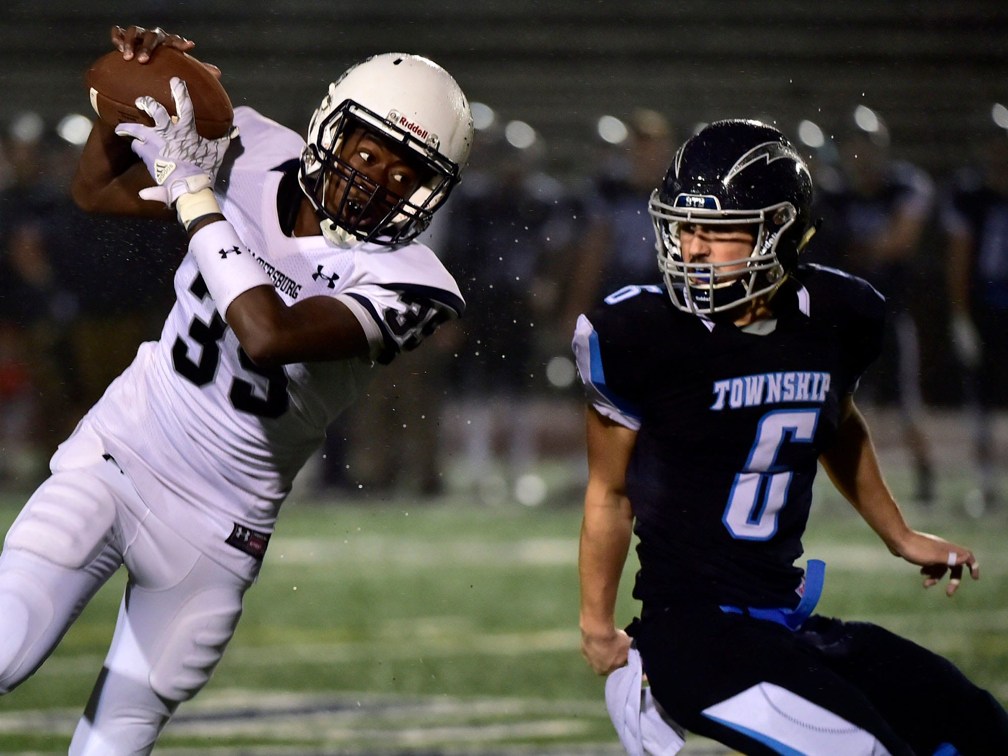 Chambersburg's DaQuan Rogers (35) catches a pass over Manheim Central's Brent Benjamin. Chambersburg Trojans dropped a close game 20-17 to Manheim Township Blue Streaks in the rain during PIAA District 3 playoff football on Friday, Nov. 2, 2018.