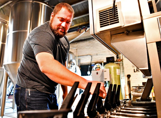Josh Hoke, of Liquid Hero Brewery, adjusts valves as The York City Six, which includes: Mudhook Brewing Company, Liquid Hero Brewery, Crystal Ball Brewing Company, Collusion Tapworks, Gift Horse Brewing Company and Old Forge Brewing Company debut their collaborative efforts to craft a pilsner at Liquid Hero Brewery in York City, Saturday, Nov. 3, 2018. The brew is expected to be matured by the end of the year and will be available at each of the six breweries where one dollar for each glass sold will be donated to the York City Police Department. Dawn J. Sagert photo