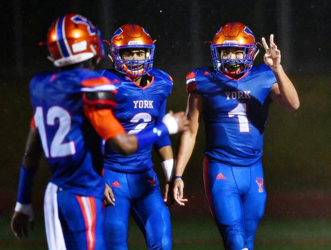 From left, York High's Rob Rideout, Tobee Stokes, and Dayjure Stewart celebrate a touchdown in a game earlier this season. Dawn J. Sagert photo