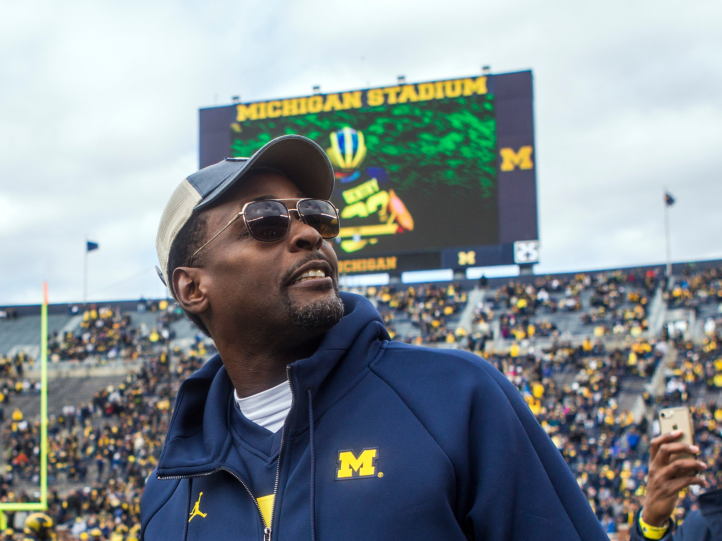 Former Michigan basketball player Chris Webber, right, on the Michigan Stadium field prior to an NCAA college football game against Penn State in Ann Arbor, Mich., Saturday, Nov. 3, 2018. Michigan is making Webber an honorary captain for the game. (AP Photo/Tony Ding)