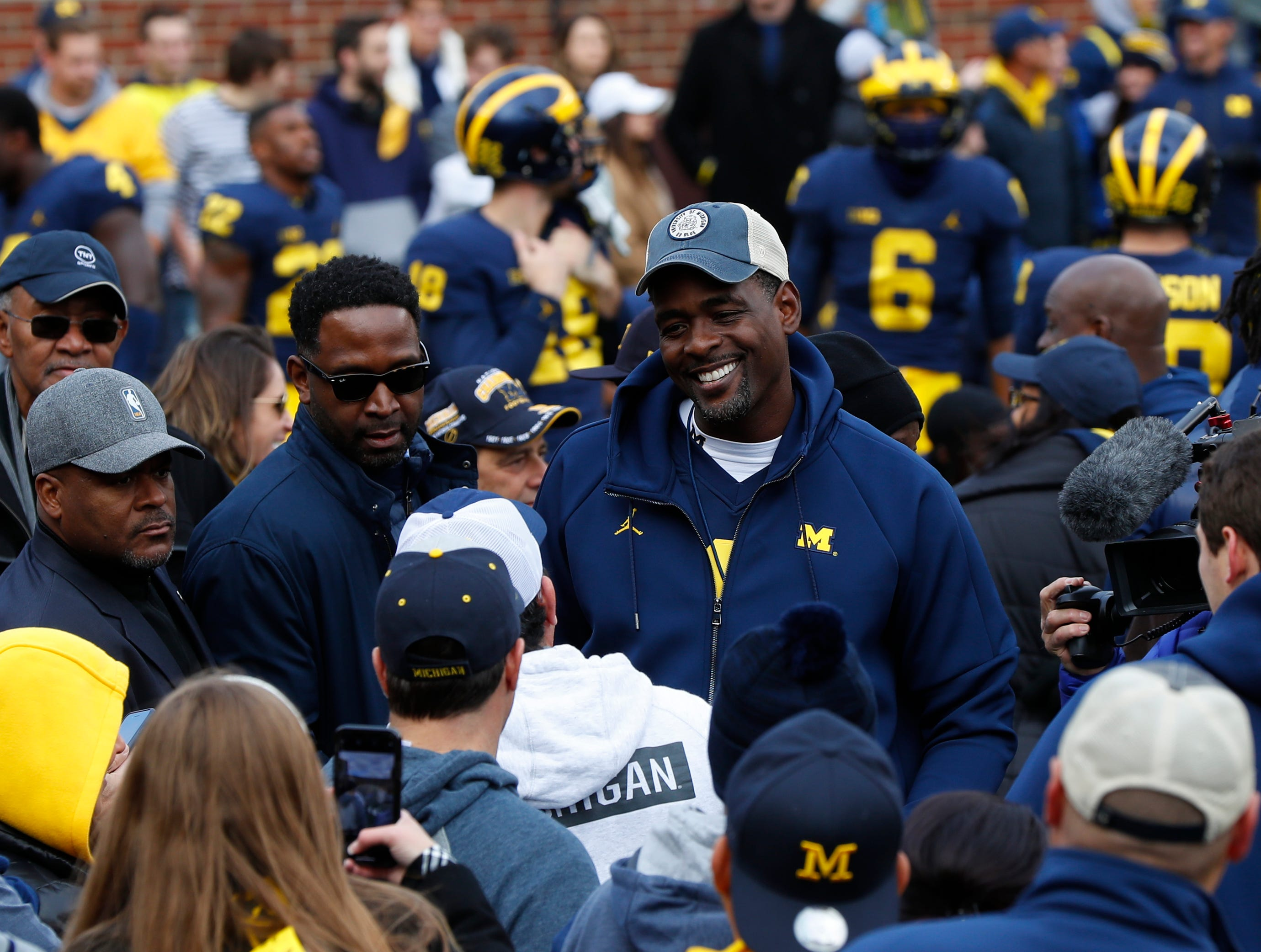 Chris Webber, a former basketball player, talks on the sidelines before an NCAA college football game against the Penn State in Ann Arbor, Mich., Saturday, Nov. 3, 2018. (AP Photo/Paul Sancya)