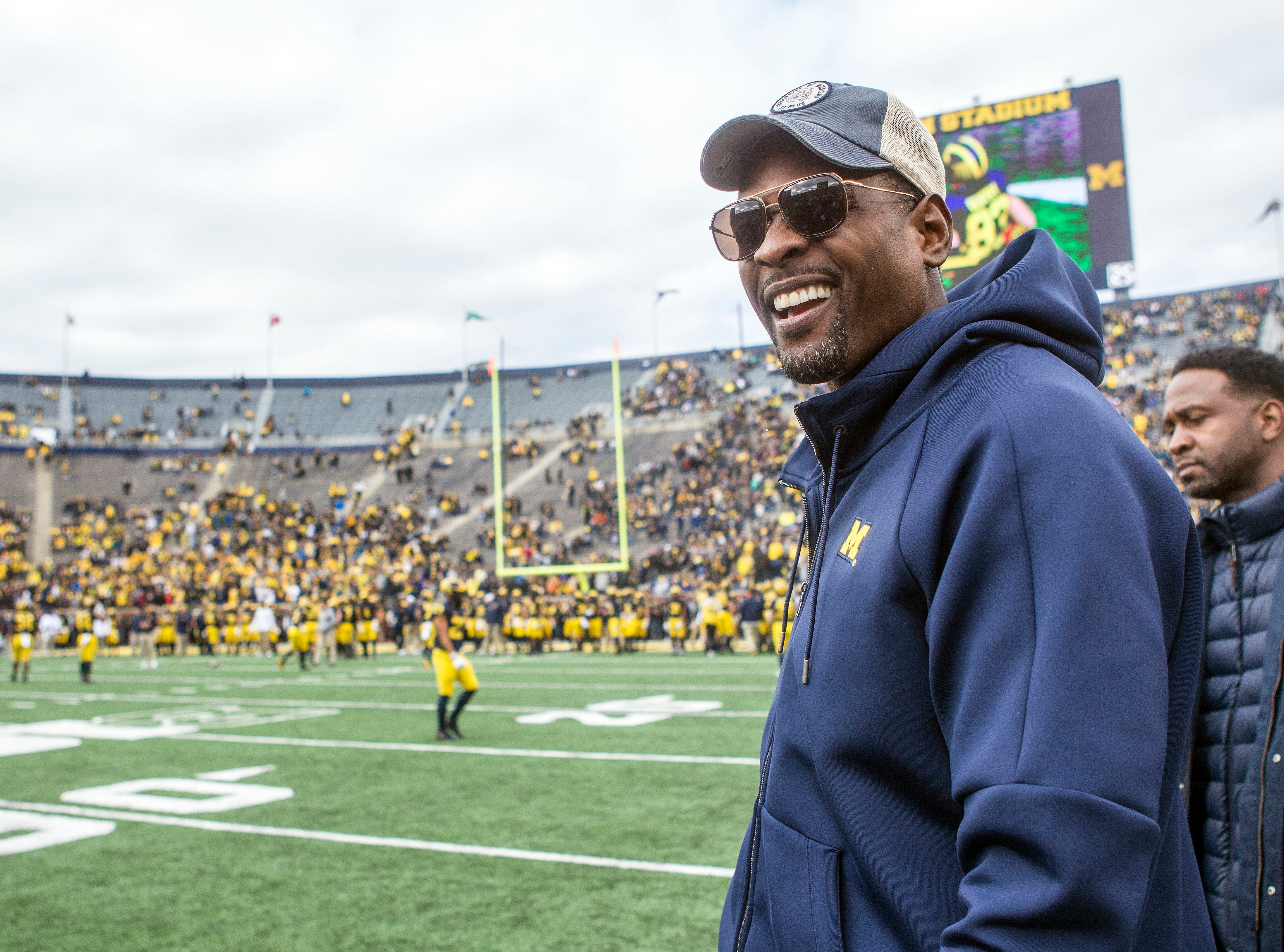 Former Michigan basketball player Chris Webber, right, watch pregame warmups on the Michigan Stadium field prior to an NCAA college football game against Penn State in Ann Arbor, Mich., Saturday, Nov. 3, 2018. Michigan is making Webber an honorary captain for the game. (AP Photo/Tony Ding)