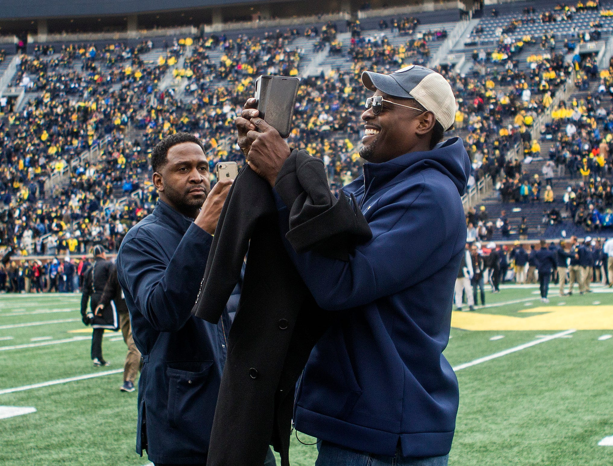 Former Michigan basketball player Chris Webber, center, takes photos with his phone on the Michigan Stadium field prior to an NCAA college football game against Penn State in Ann Arbor, Mich., Saturday, Nov. 3, 2018. Michigan is making Webber an honorary captain for the game. (AP Photo/Tony Ding)