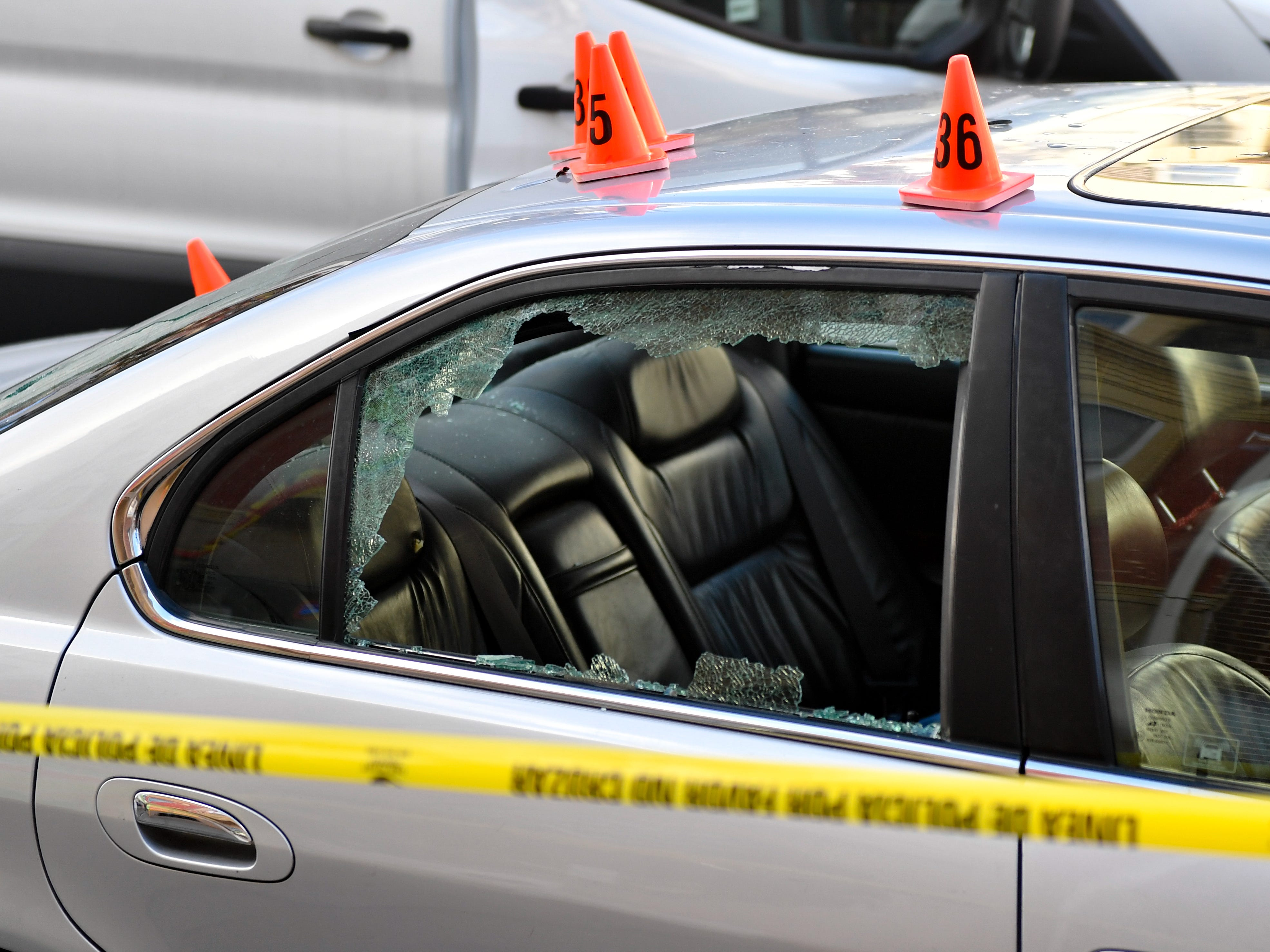 Police officers place small orange cones where bullet holes can be found on the cars, November 3, 2018.