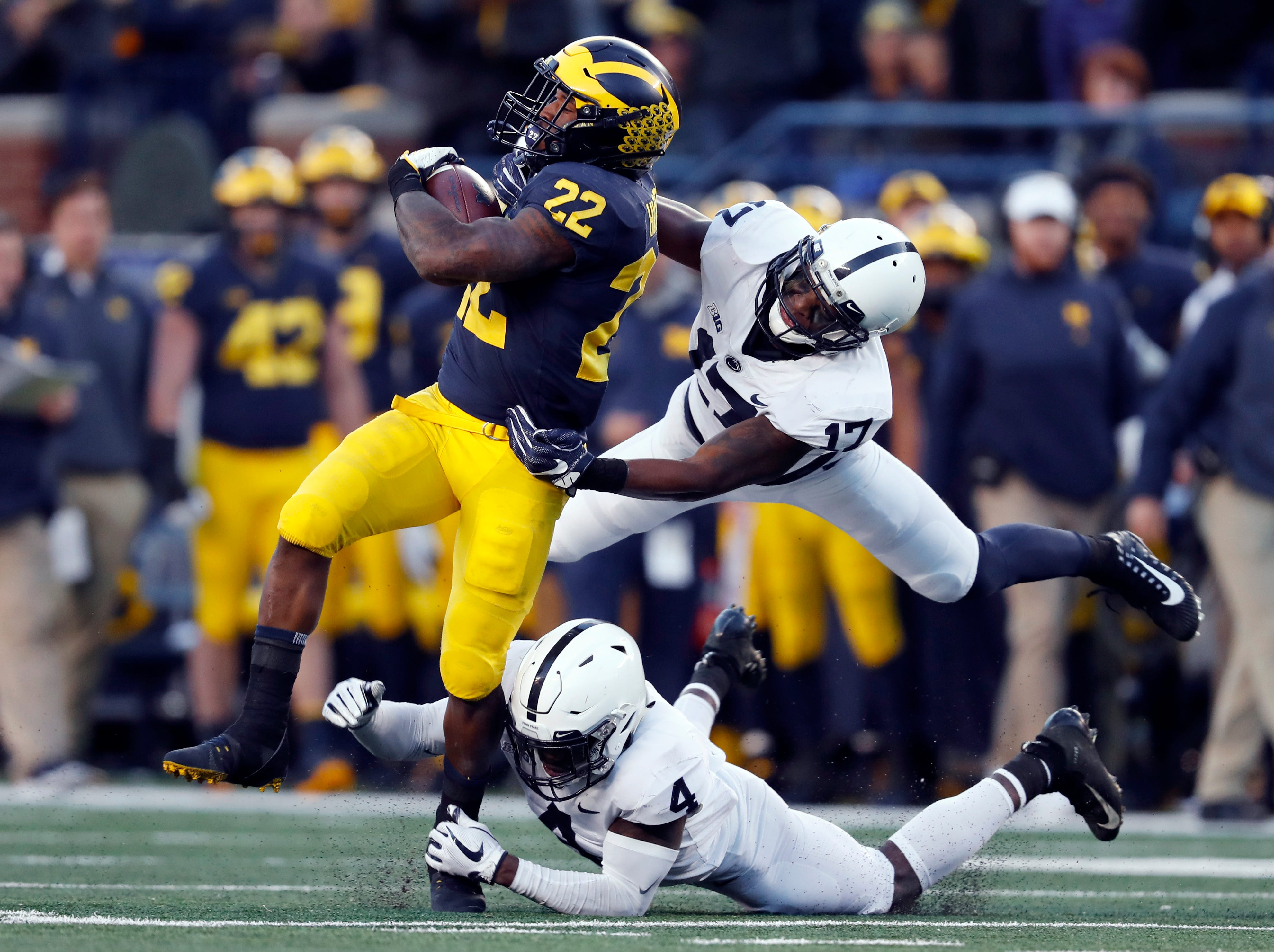 Michigan running back Karan Higdon (22) is tackled by Penn State safety Nick Scott (4) and Garrett Taylor (17) in the second half of an NCAA college football game in Ann Arbor, Mich., Saturday, Nov. 3, 2018. (AP Photo/Paul Sancya)