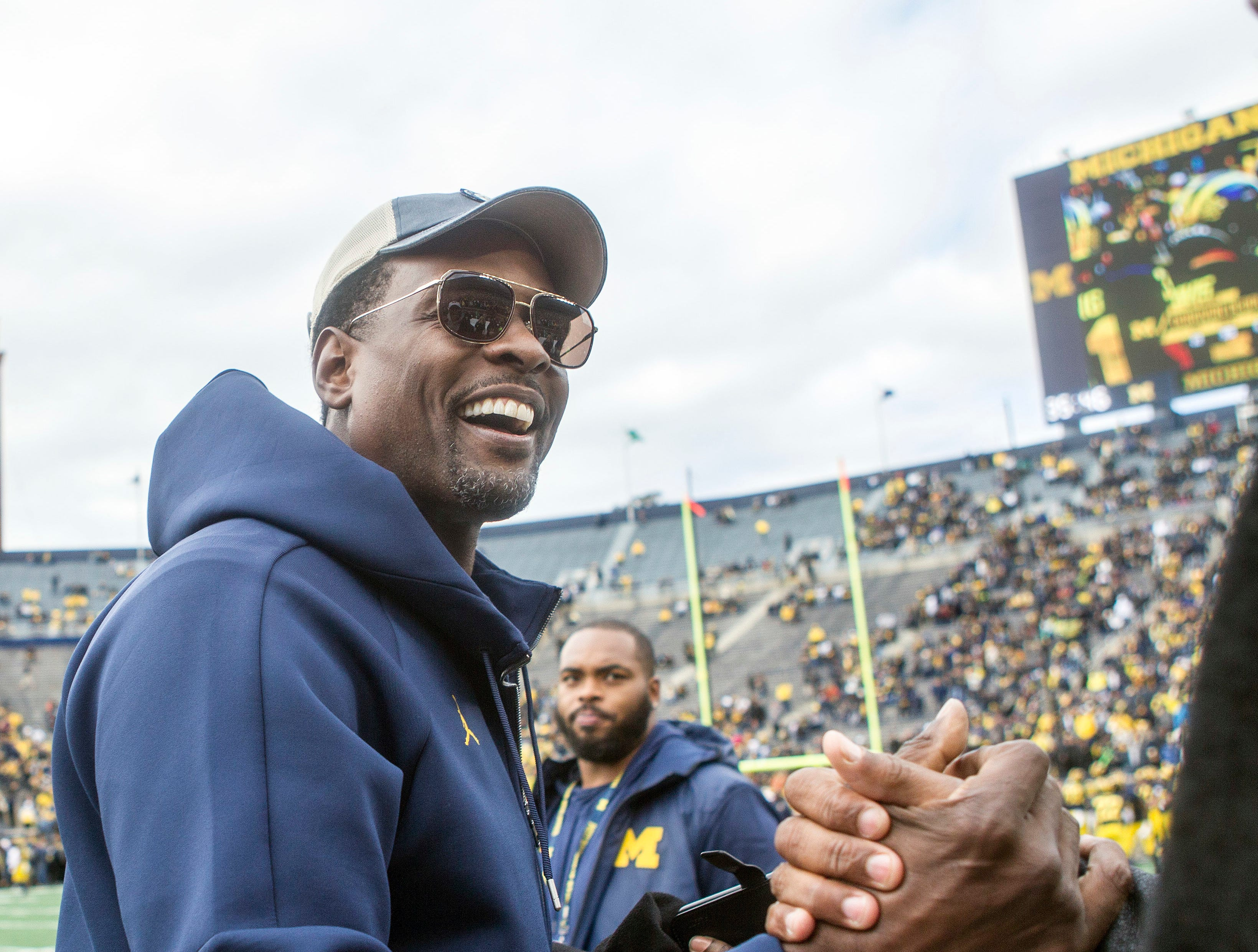 Former Michigan basketball player Chris Webber, right, greet fans on the Michigan Stadium field prior to an NCAA college football game against Penn State in Ann Arbor, Mich., Saturday, Nov. 3, 2018. Michigan is making Webber an honorary captain for the game. (AP Photo/Tony Ding)