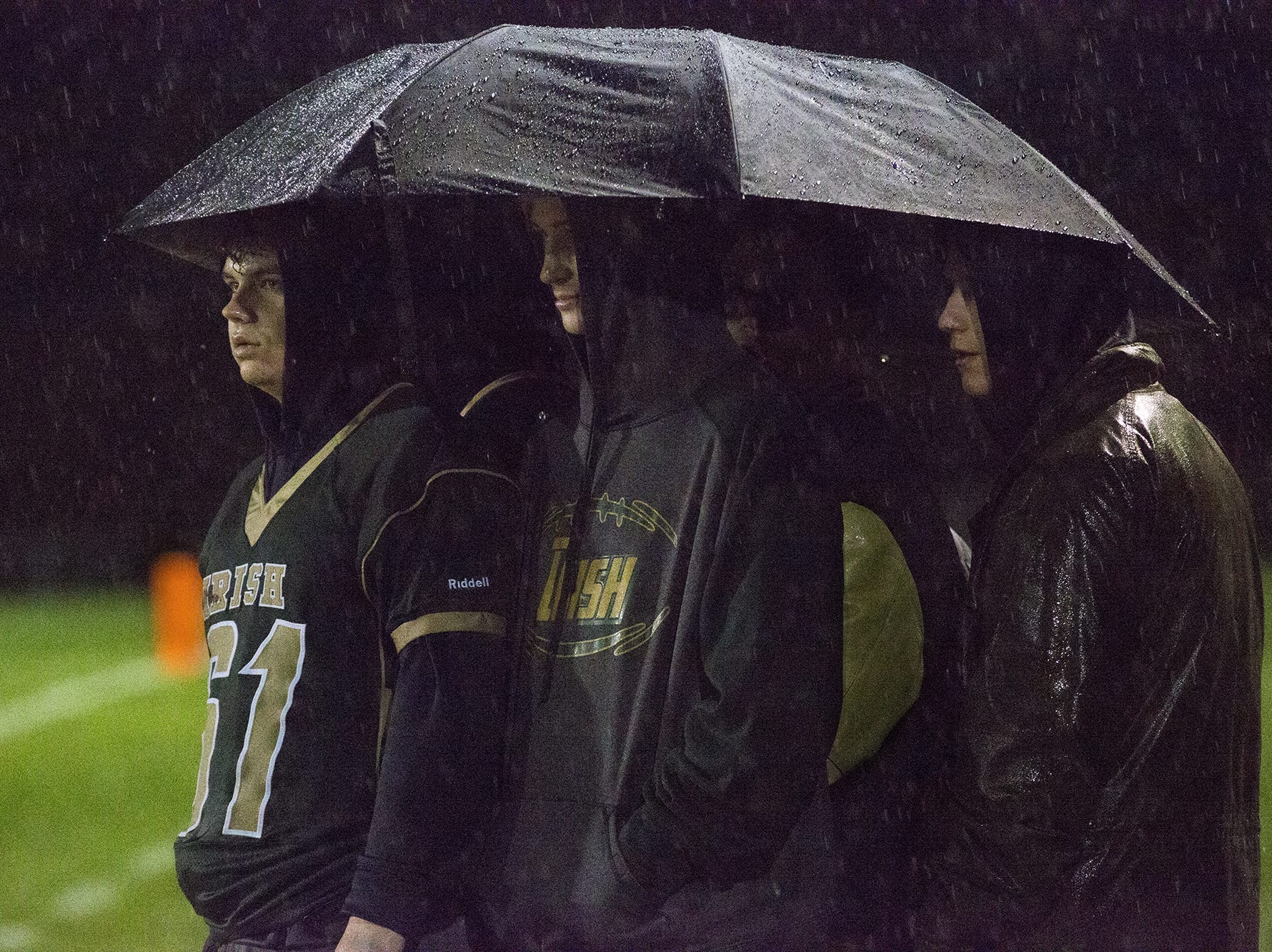 A group of boys share an umbrella on the York Catholic sideline. York Catholic defeats Steelton-Highspire 21-0 in a District 3 Class 2A semifinal football game at York Catholic High School in York, Friday, November 2, 2018.