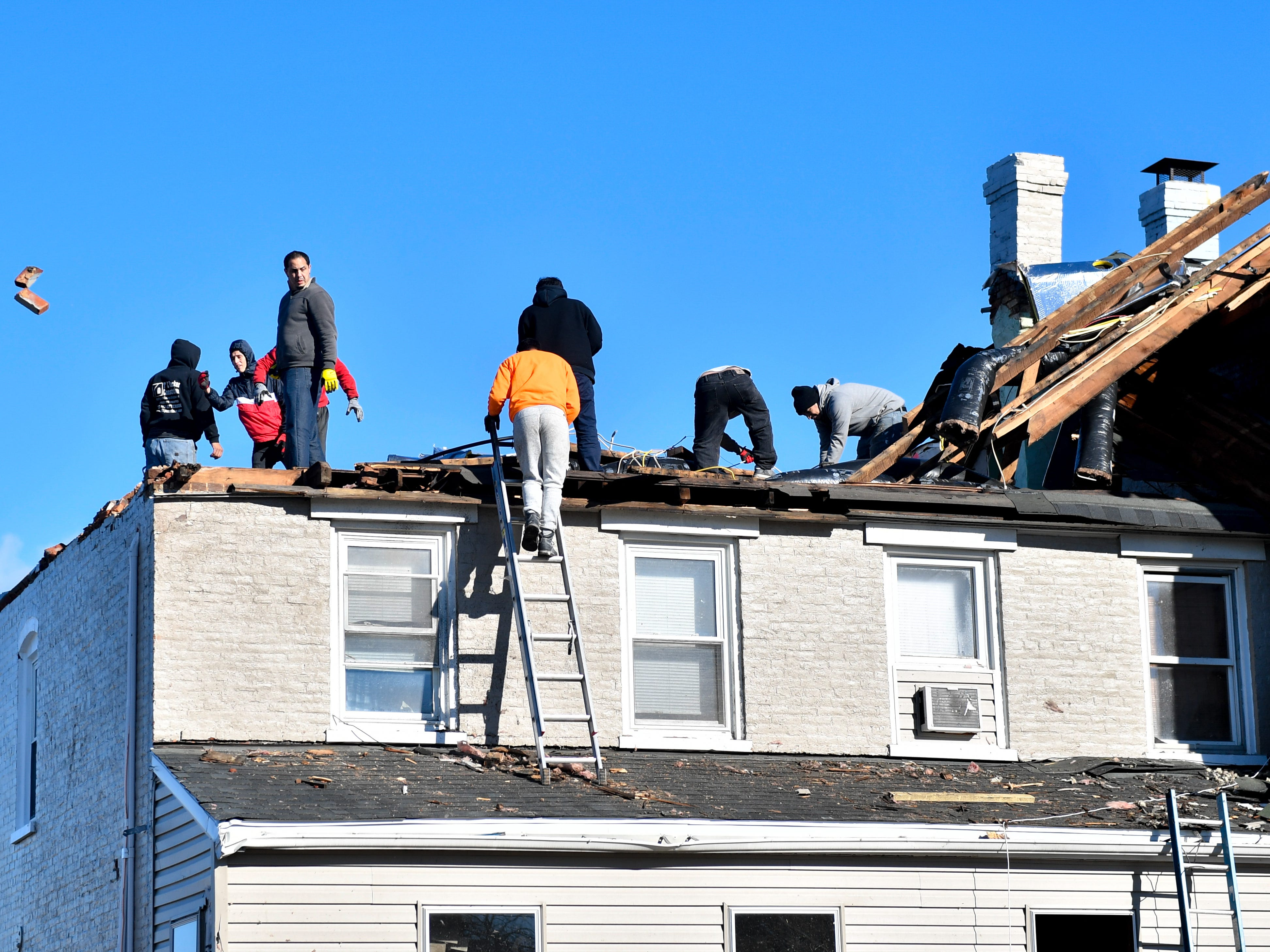 Workers salvage the roof and toss any debris off, November 3, 2018.