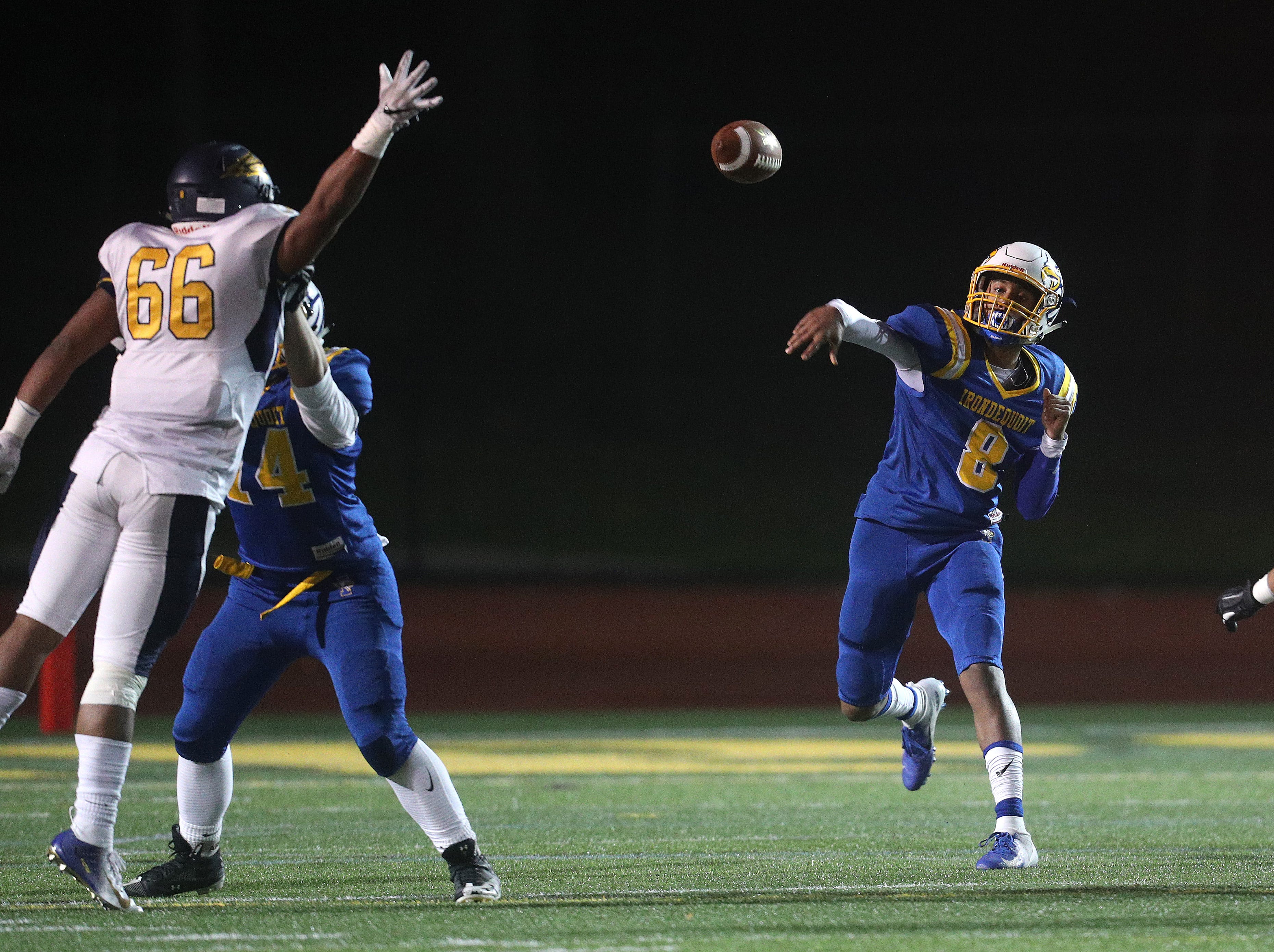 Irondequoit quarterback Freddy June Jr. steps into a throw over Victor's Jon Crowley (66).
