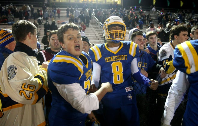 Freddy June Jr (8) celebrates with fans after Irondequoit came from behind to be a Victor 21-14 and win the Class A title.