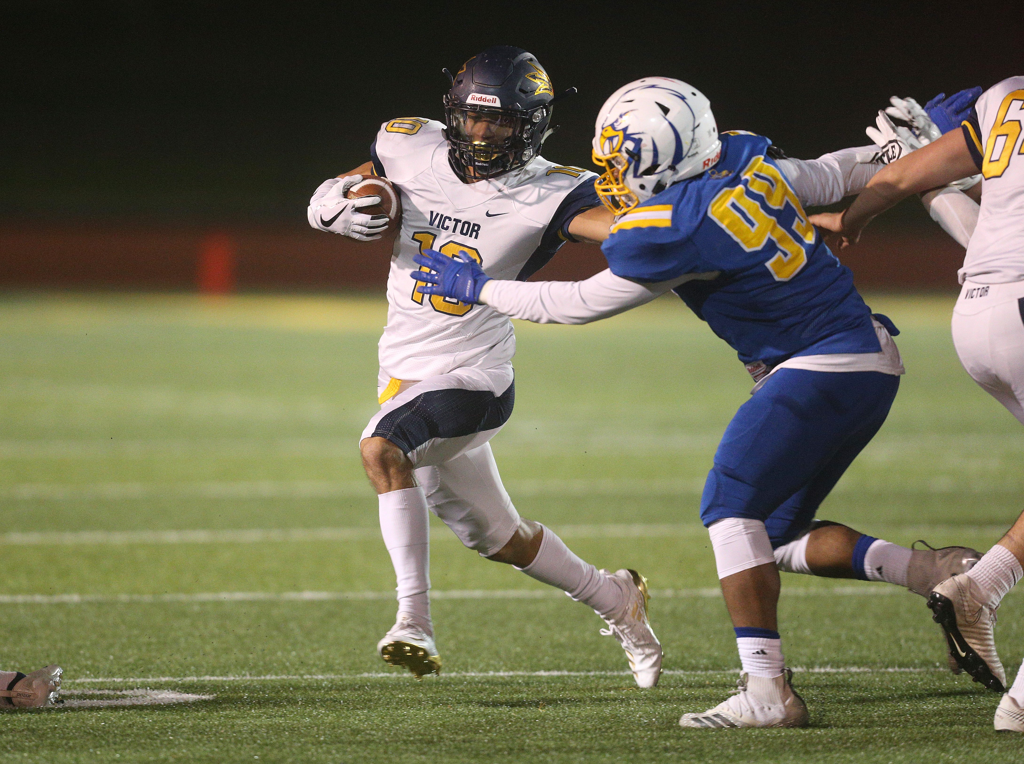 Victor's Kordell Jackson tries to fight off a tackle by Irondequoit's Cameron Martin (99).