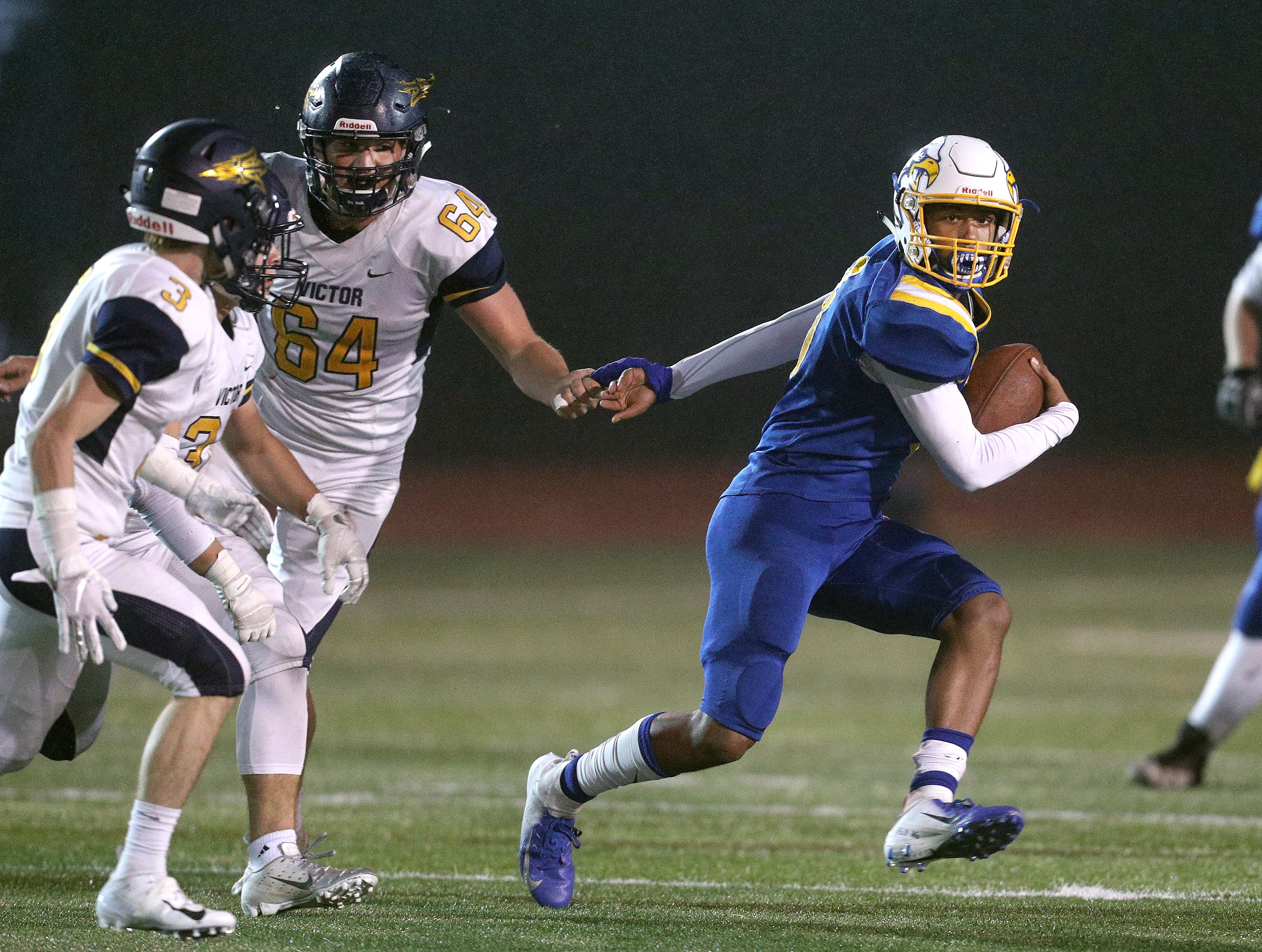 Irondequoit's Freddy June Jr. tries to slip a tackle by Victor's Sam Castiglia (64).