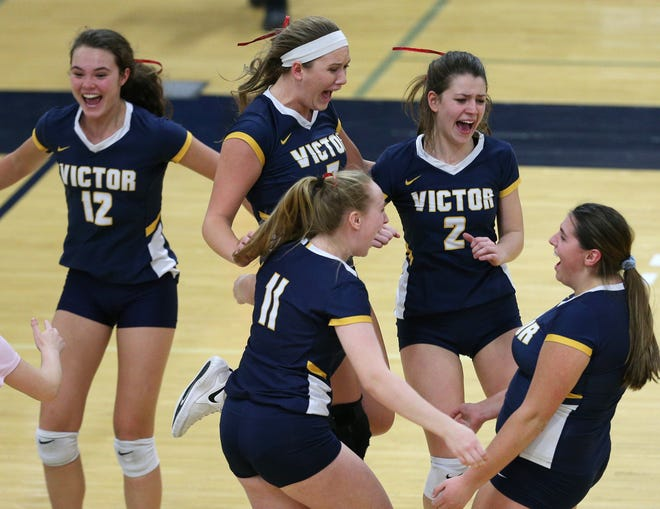 Members of the Victor High School volleyball team celebrate their win over Mercy in the 2018 Section V Class AA championship match.