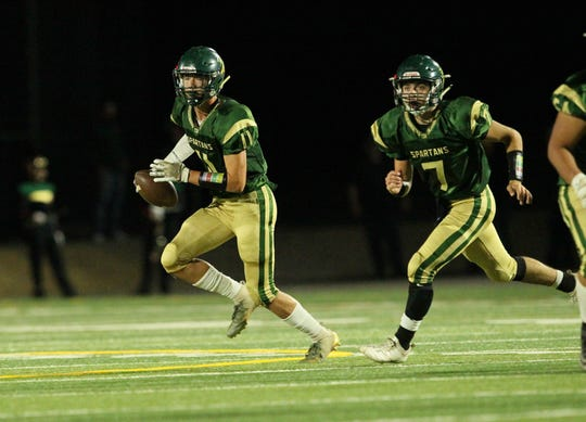 Red Bluff receiver Logan Robertson (left) runs with the ball alongside quarterback Eli Wehbey during the Spartans' 28-21 win over Enterprise on Friday, Nov. 2.